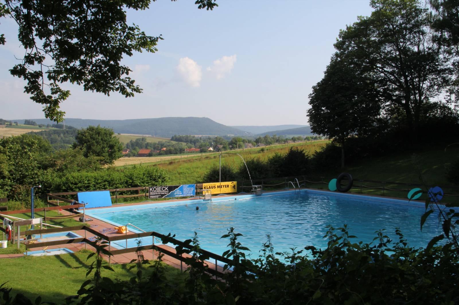Blick über ein Schwimmbad, im Hintergrund ein Höhenzug