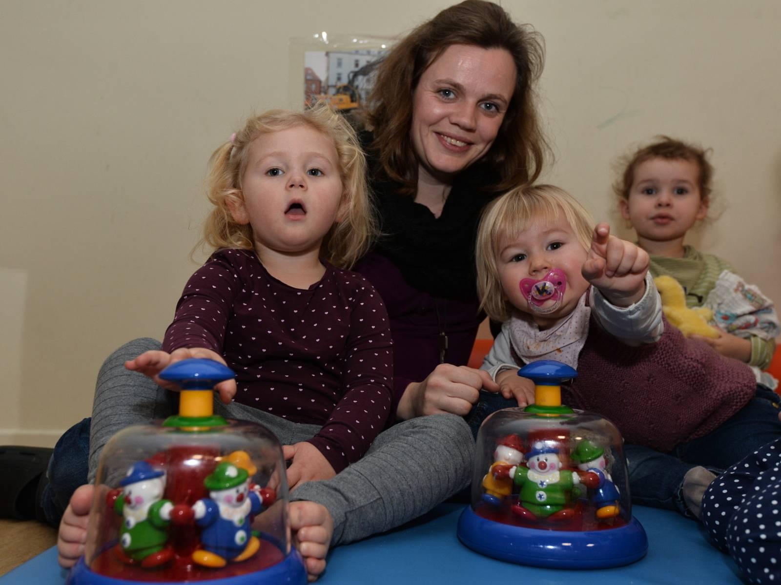 Krippenkinder mit einer Erzieherin und Kinderkreiseln.