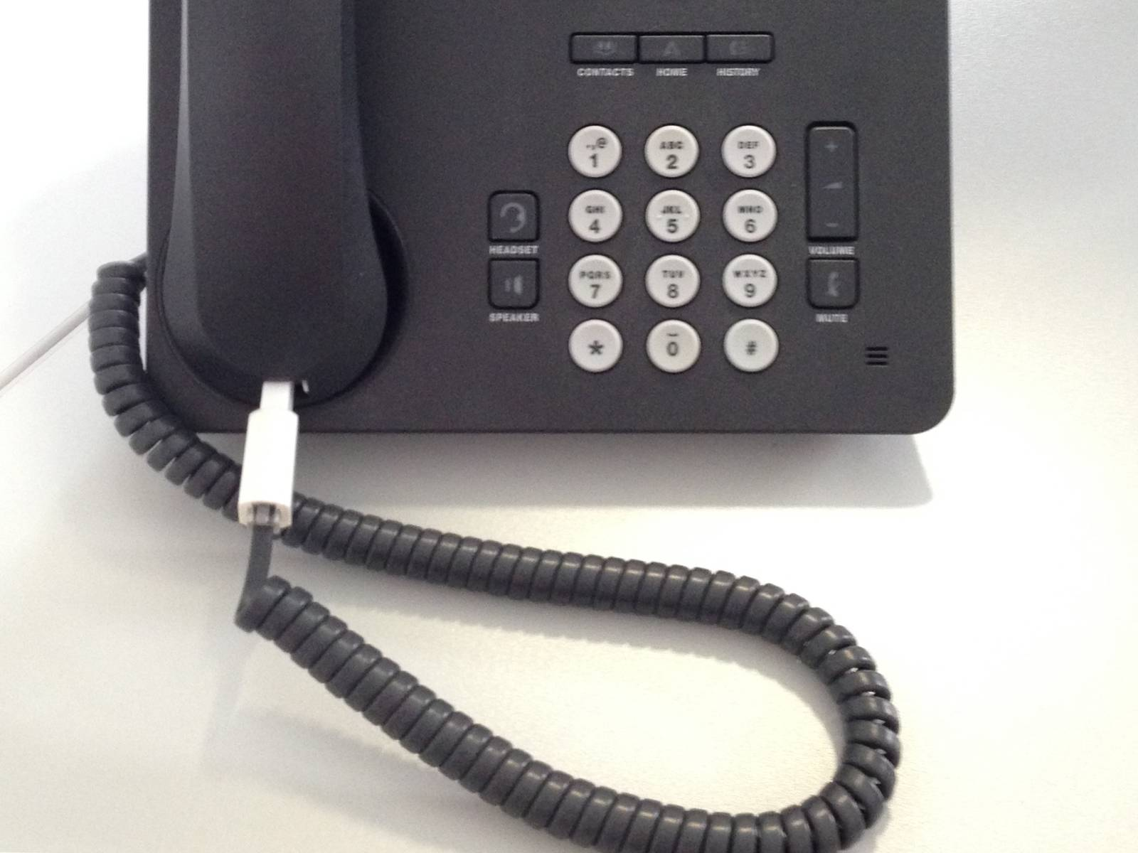 Ein schwarzes altes Telefon mit Tasten und verkabeltem Hörer.