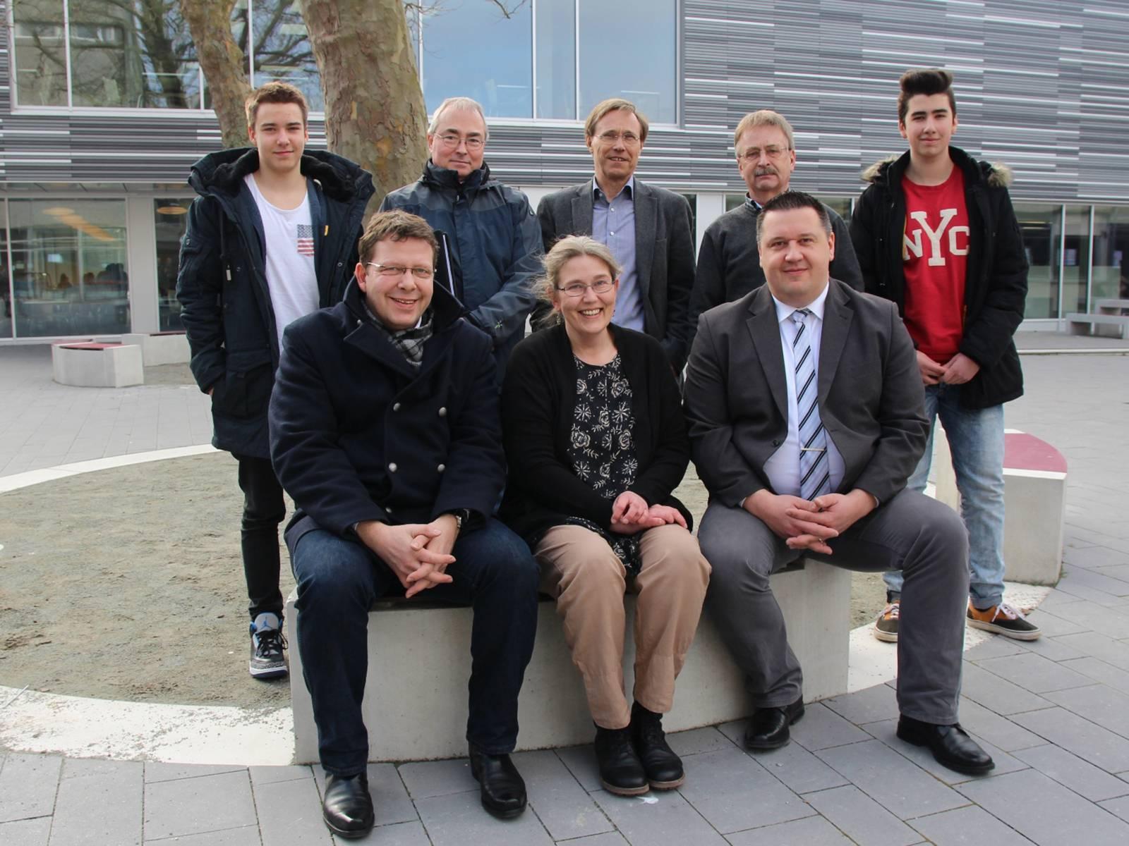 Eine Gruppe von acht Personen, sieben Männer und eine Frau, die vor einem Gebäude mit moderner Fassade stehen und sitzen.