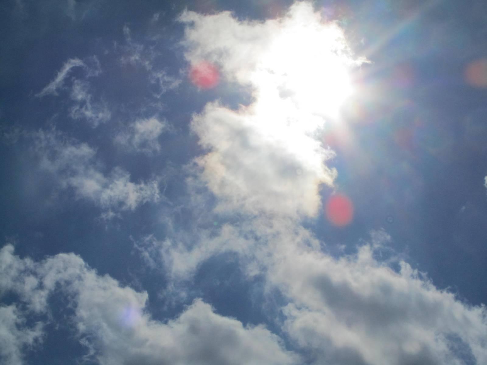 Blick in den Himmel. Vor die Sonne haben sich ein paar weiße Wolken geschoben.