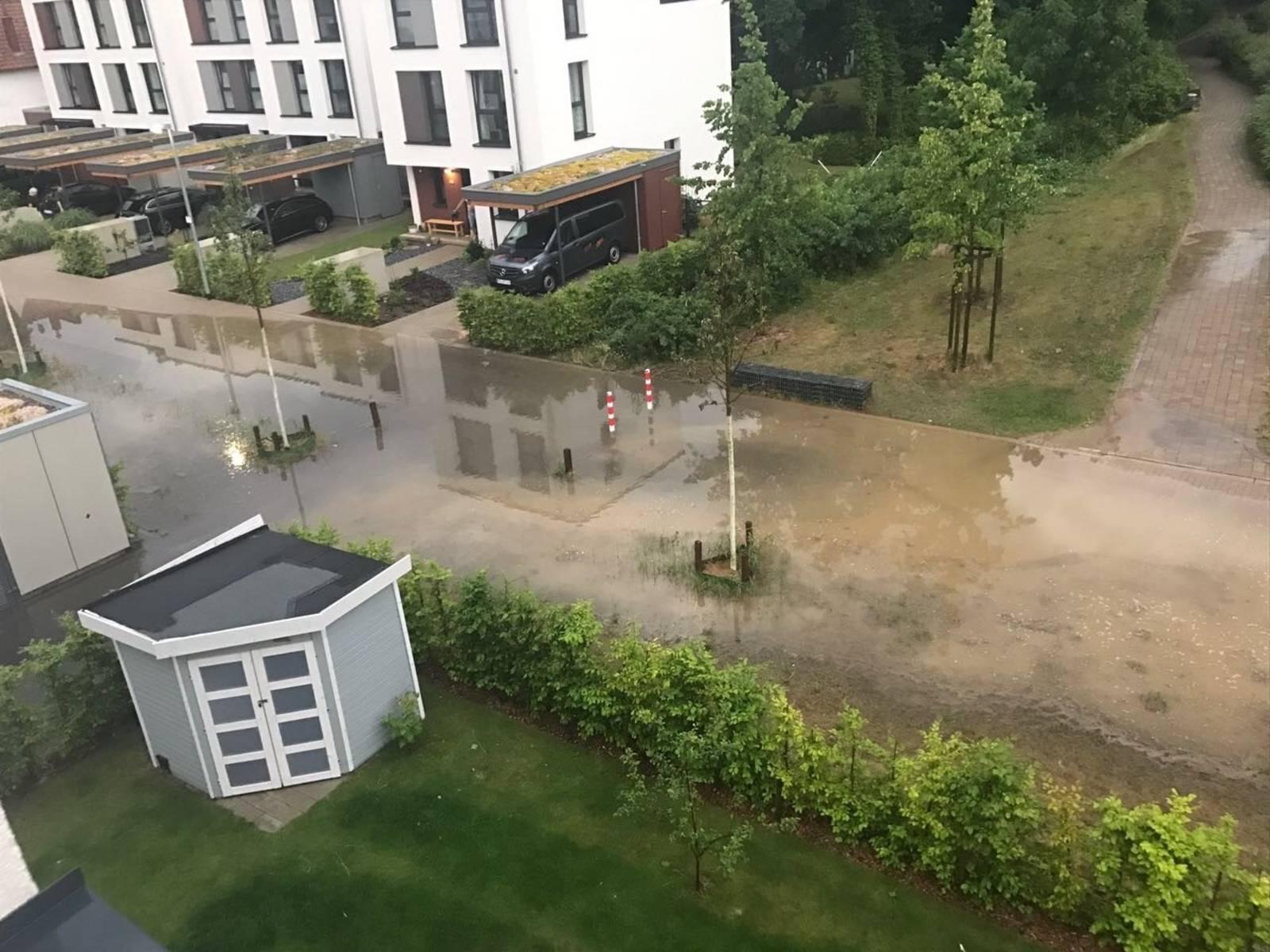 Grundstückseinfahrten, Teile einer Straße und eines geflasterten Fussweges, die nach einen Starkregen unter Wasser stehen