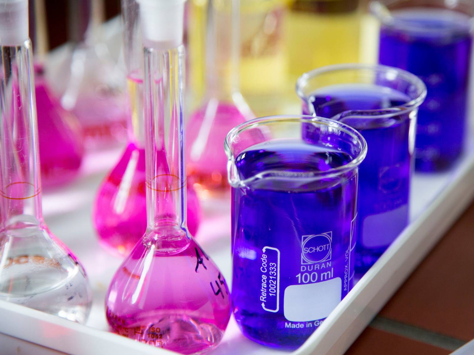 Kolbengefäße mit schmalem Hals (links) und zylindrische Becher mit Ausguss (rechts). Die enthaltenen Flüssigkeiten sind in den Farben Rosa (Messkolben) und Blau (Bechergläser) eingefärbt.