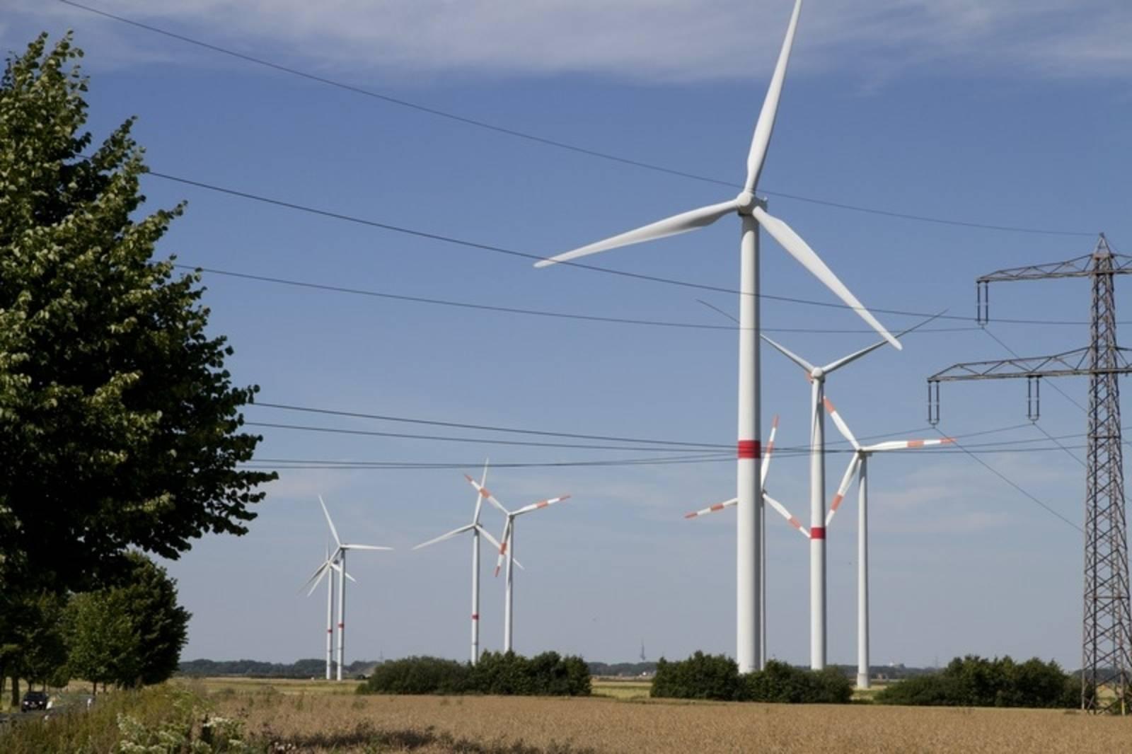 Landschaft mit Windräden und Stromtrasse.