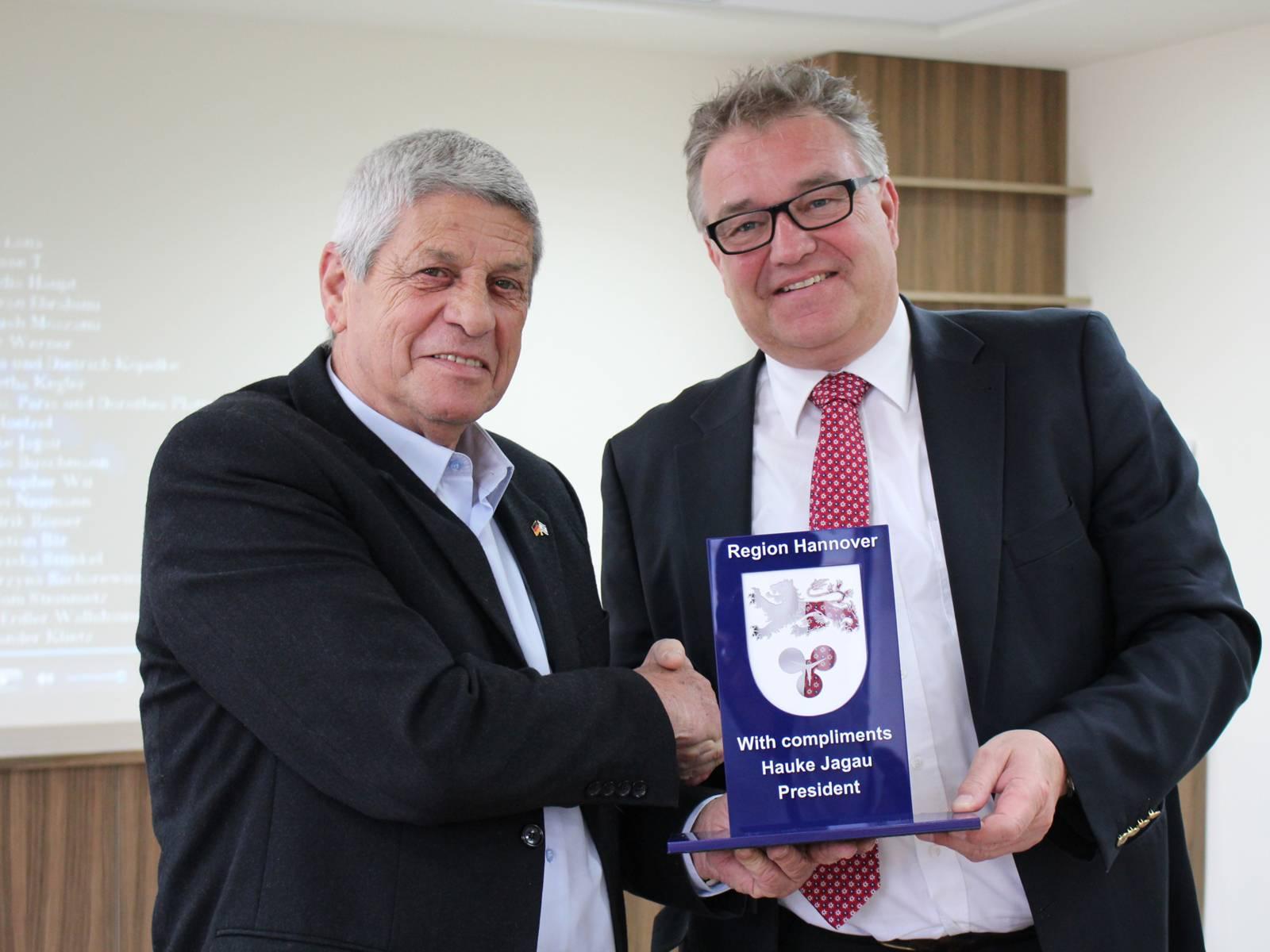 v.lks. Moti Dotan und Regionspräsident Hauke Jagau, der ein Präsent der Region Hannover überreicht