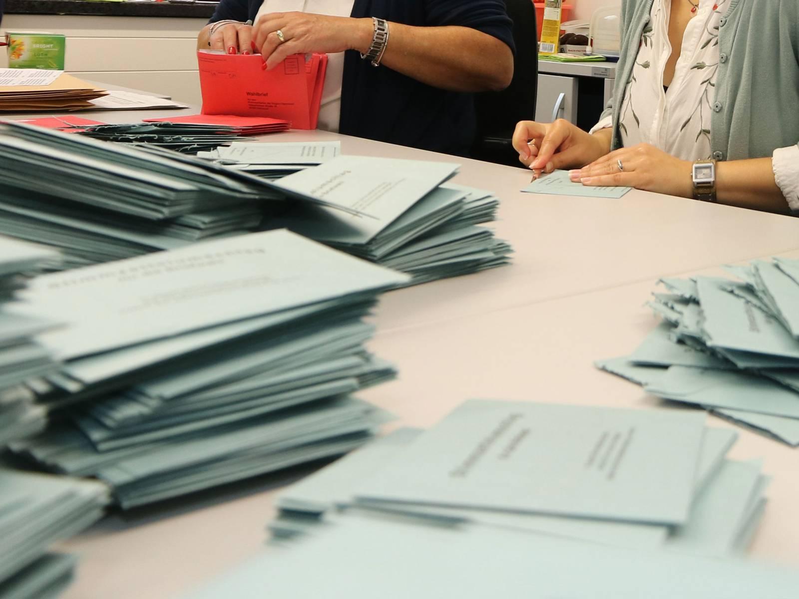 Rote und blaue Wahlumschläge und zwei Frauen, die mit der Auszählung beschäftigt sind.