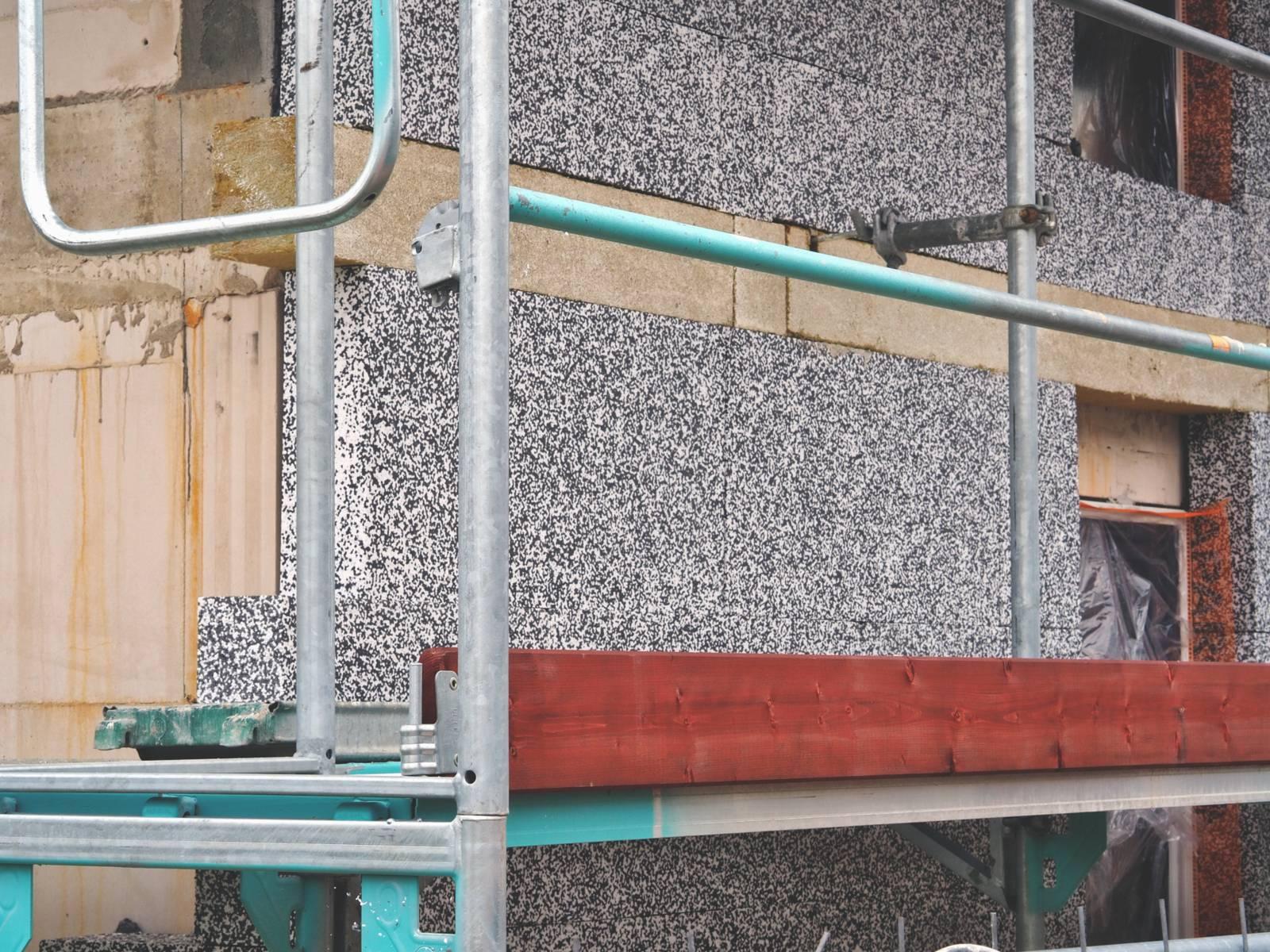 Ein Gerüst steht an einem Rohbau, an die Fassade wird Wärmedämmung angebracht.