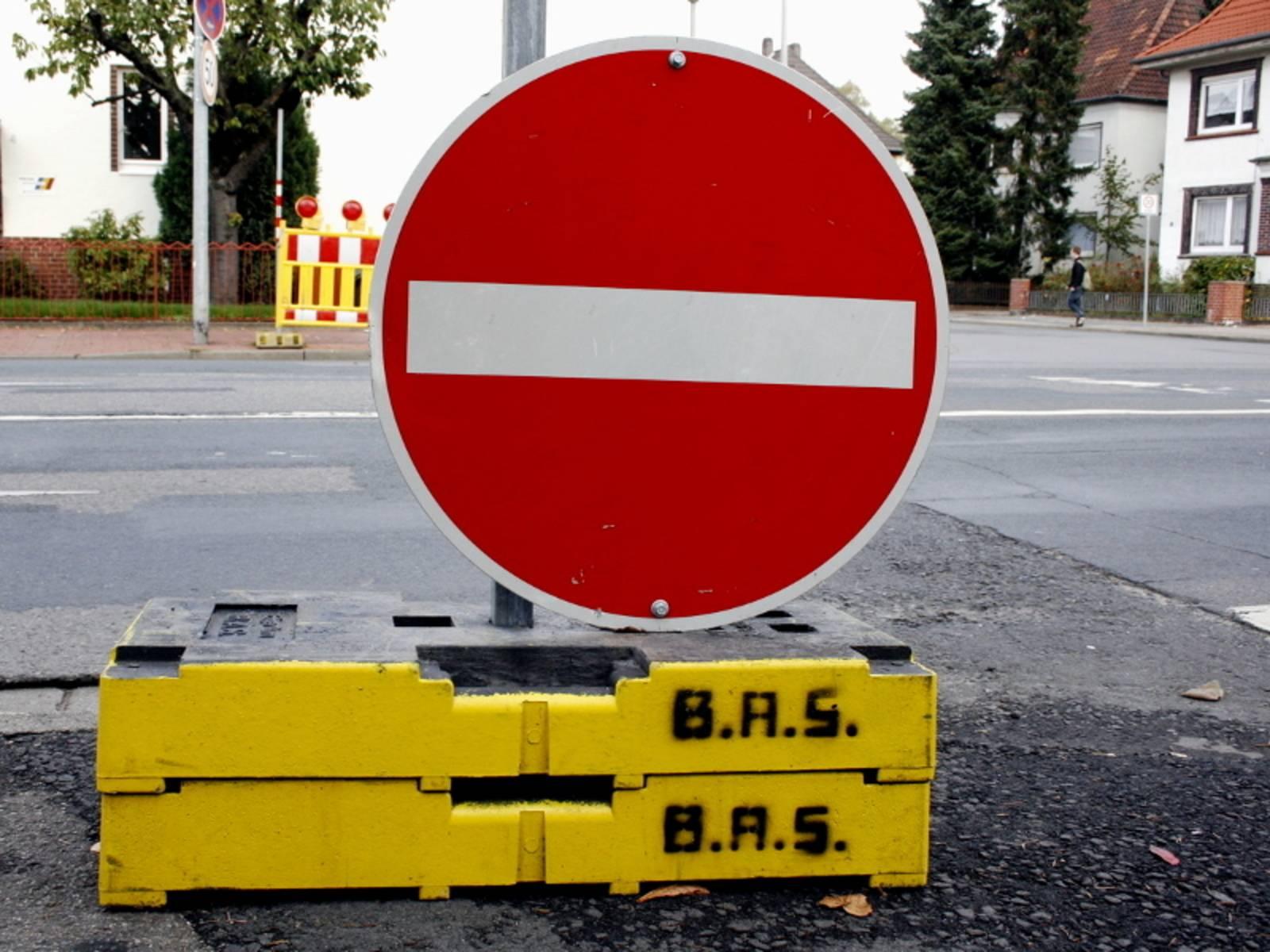 """Ein Verkehrsschild """"Verbot der Einfahrt"""" wird provisorisch von schweren Betonelementen gehalten. Im Hintergrund ist eine Straßenkreuzung zu erkennen."""