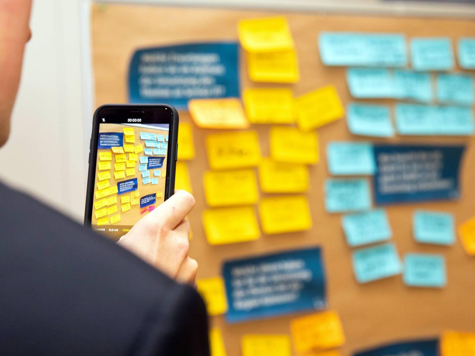 Ein Mann Film eine Metaplanwand, an der Metaplanwand pappen Zettel und Kärtchen in verschiedenen Farben und unterschiedlich beschriftet.