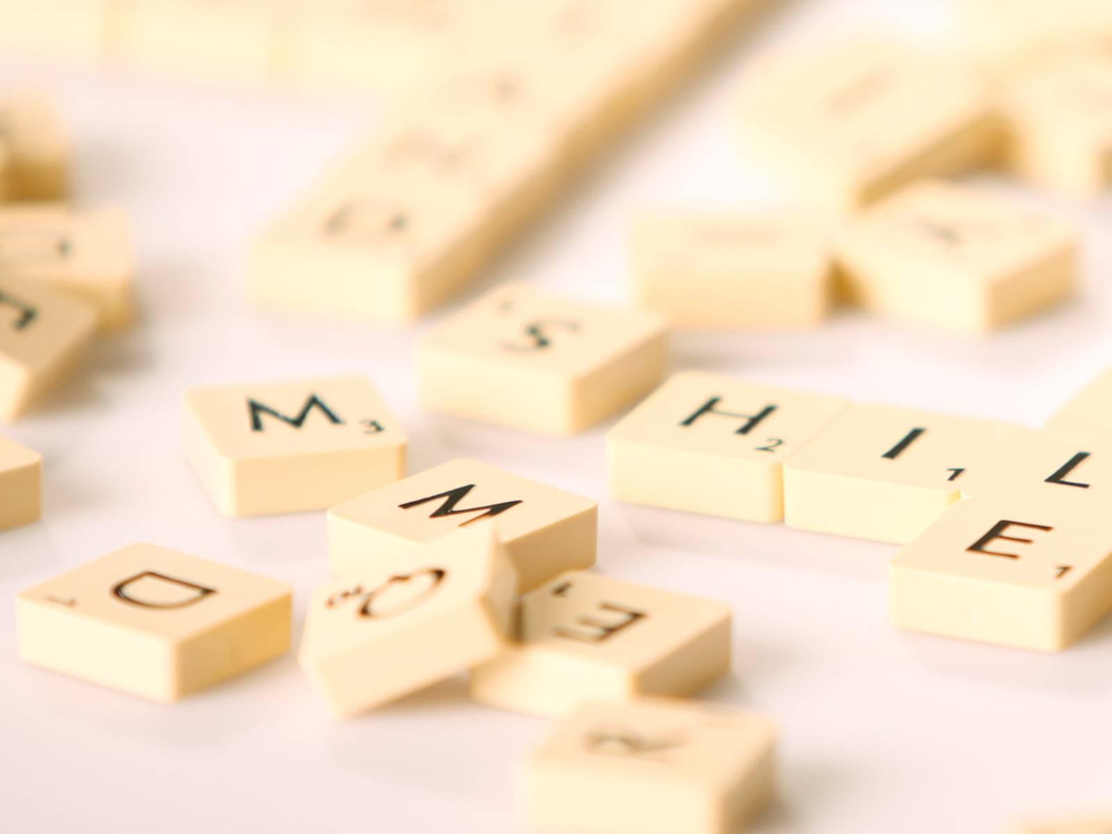 Spielsteine tragen einzelne Buchstaben und liegen durcheinander.