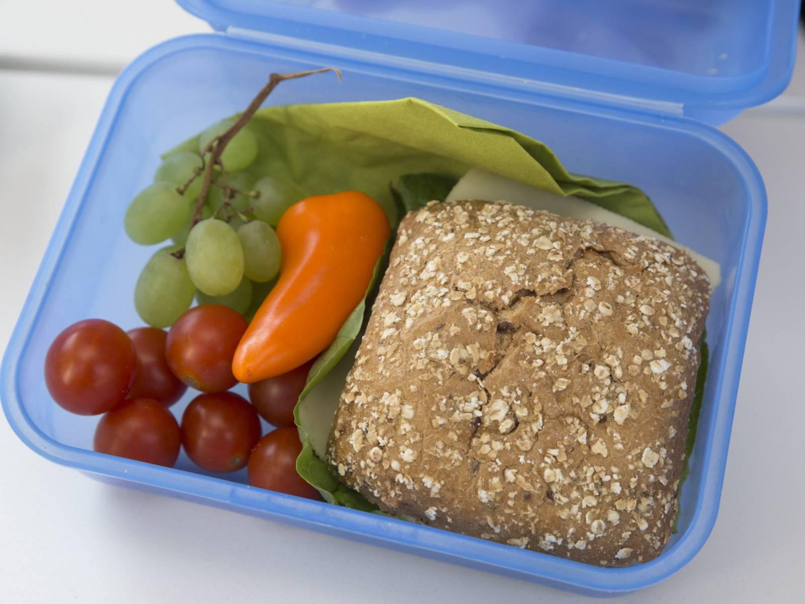 Brotdose mit Käsebrötchen, Tomaten und Weintrauben gefüllt