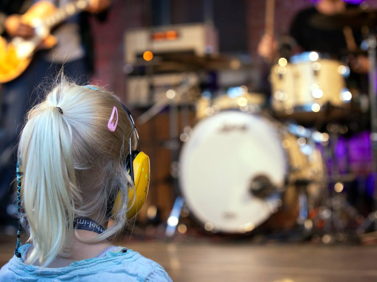 Ein Kind trägt Gehörschutz und schaut sich ein Live-Konzert an.