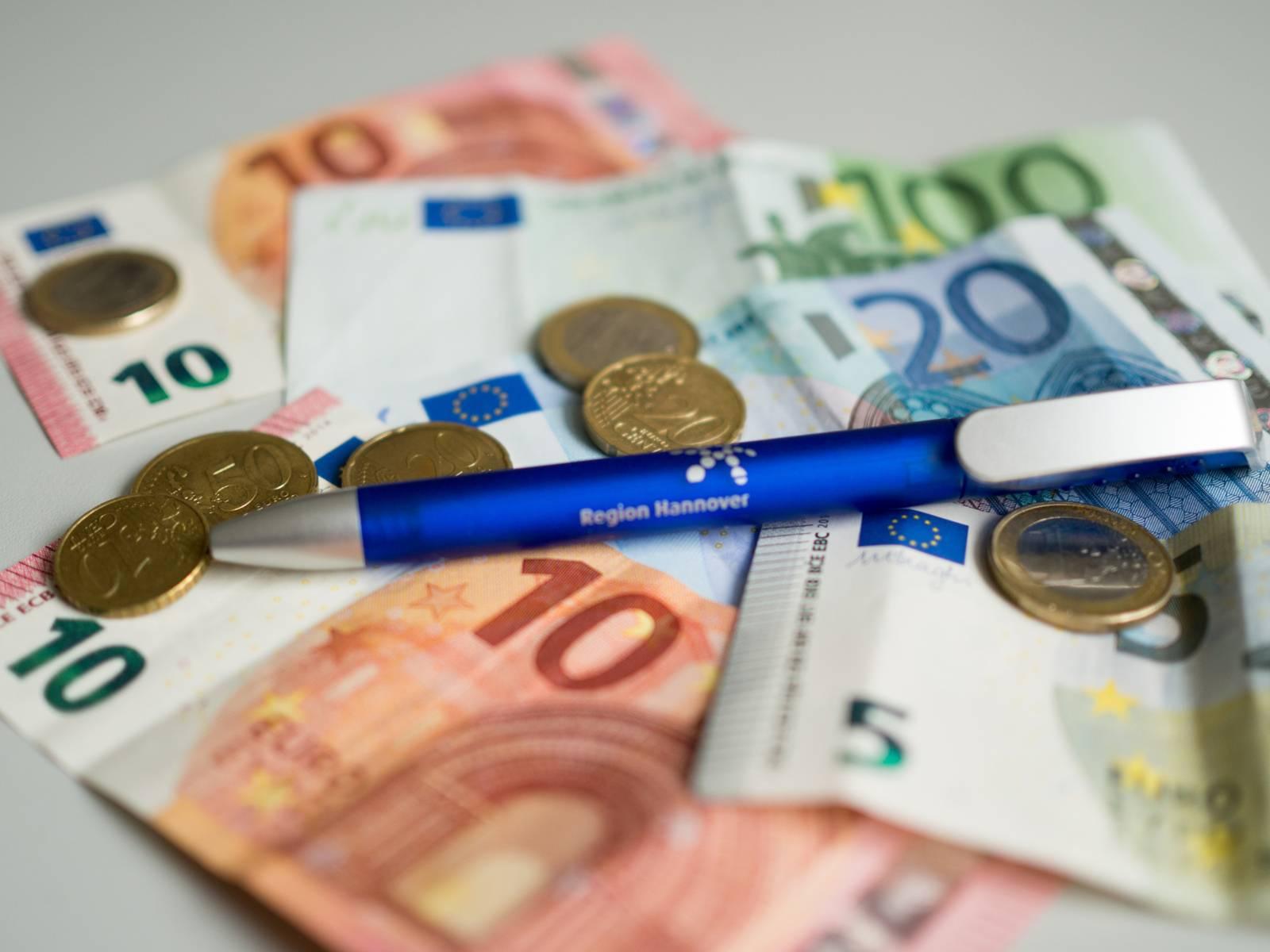 Zwei Zehneuroscheine, ein Hunderteuroschein, ein Zwanzigeuroschein, ein Fünfeuroschein, mehrere Münzen und ein blauer Kugelschreiber liegen auf einem grauen Tisch.
