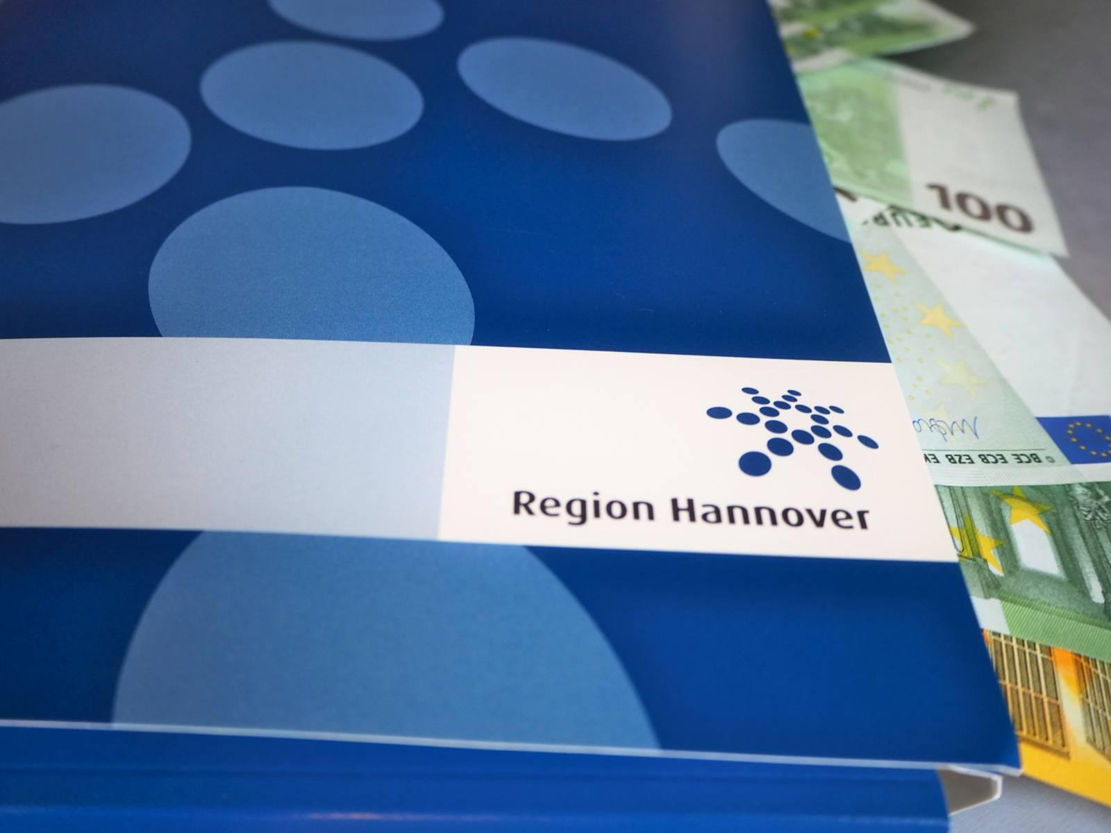 Aus einer blauen Mappe mit Regionslogo ragen Geldscheine hinaus.