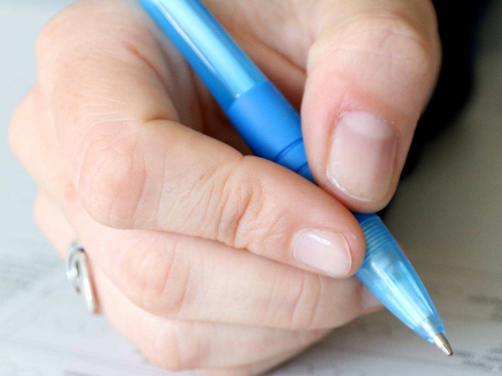 Eine Hand hält einen blauen Kugelschreiber und bewegt sich über ein Formular.