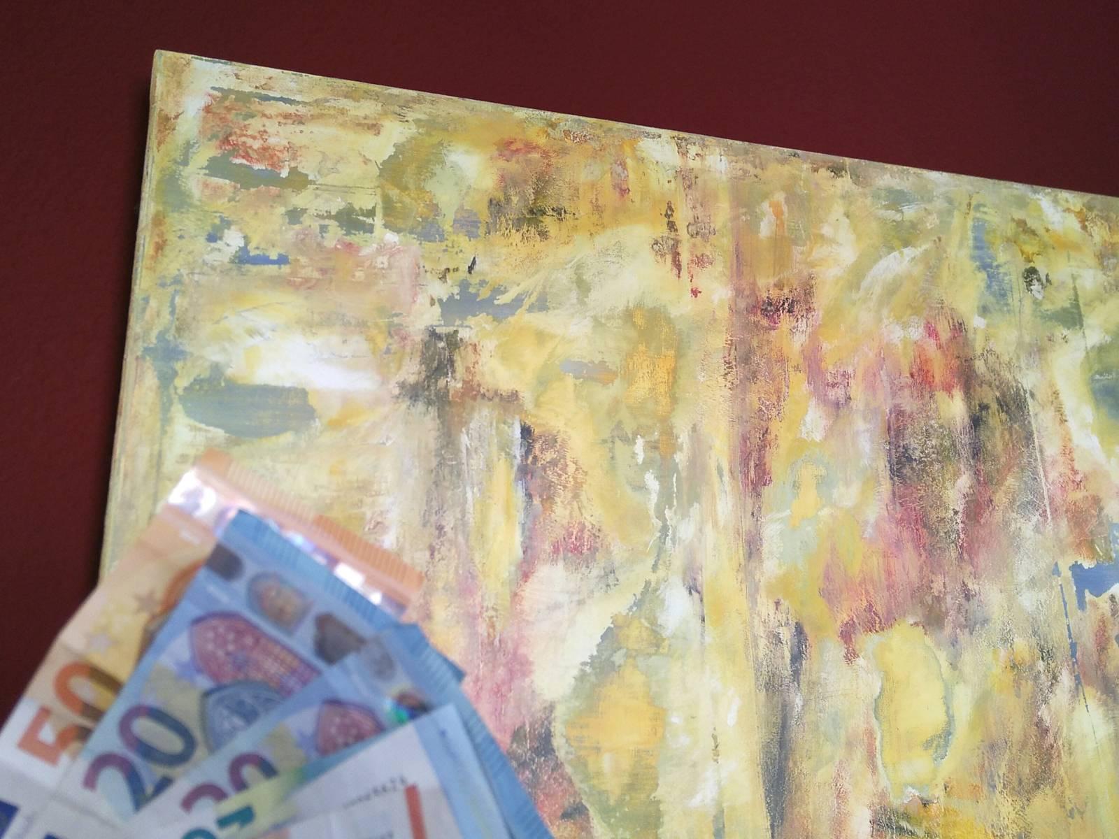Geldscheine im Vordergrund, im Hintergrund ist ein Kunstwerk.
