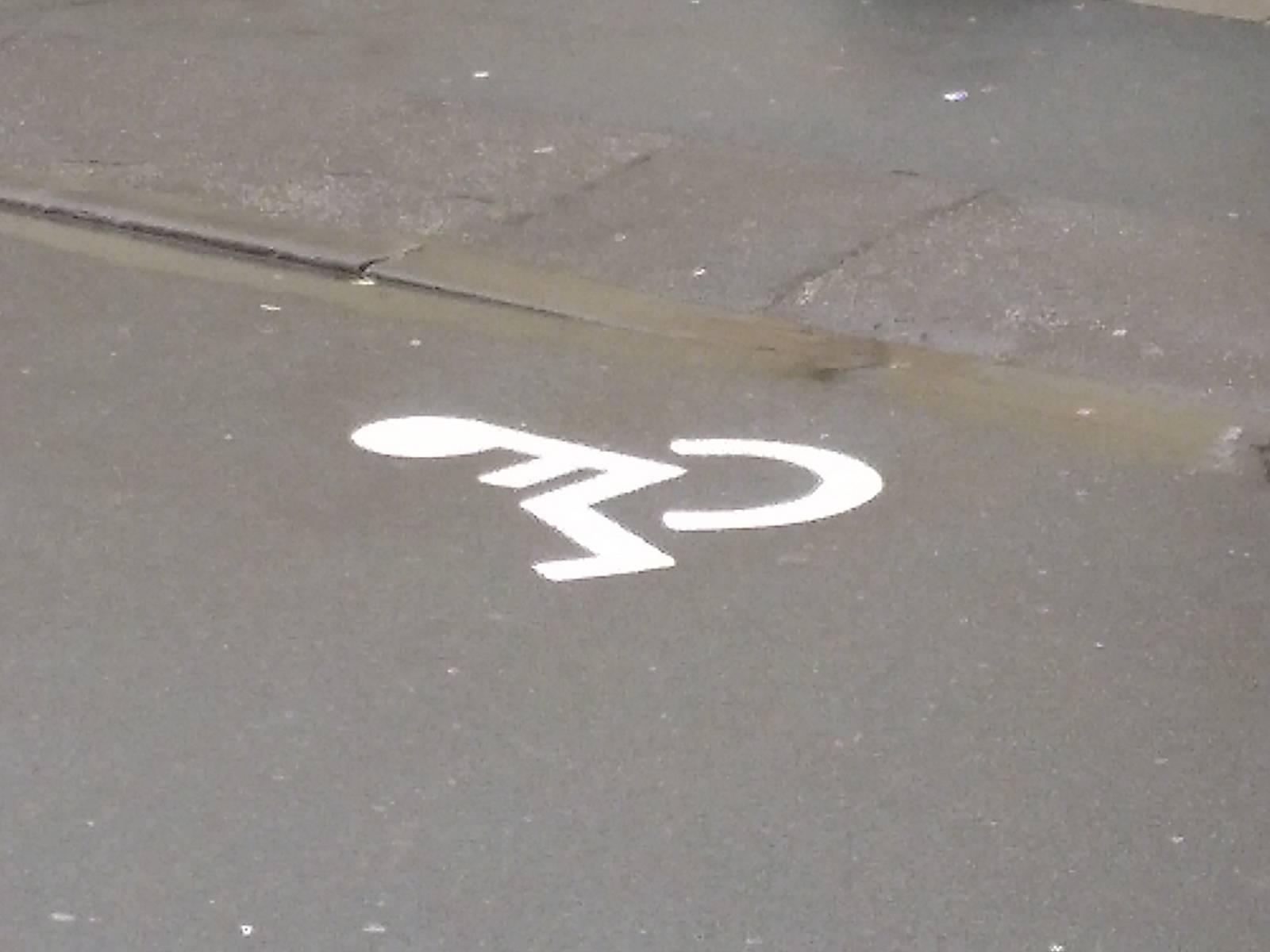 Rollstuhlfahrersymbol an einem Parkplatz
