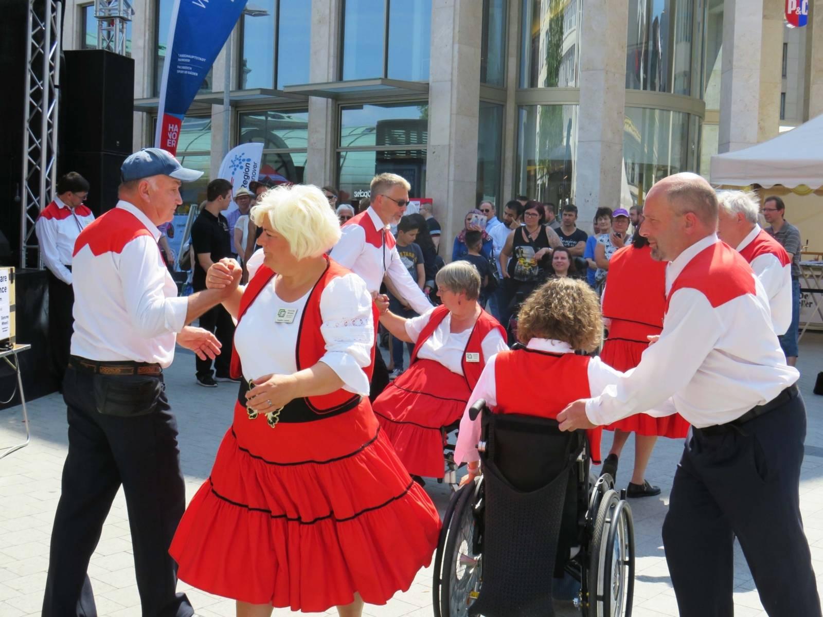 Menschen mit und ohne Rollstuhl beim Tanz auf einem Platz.