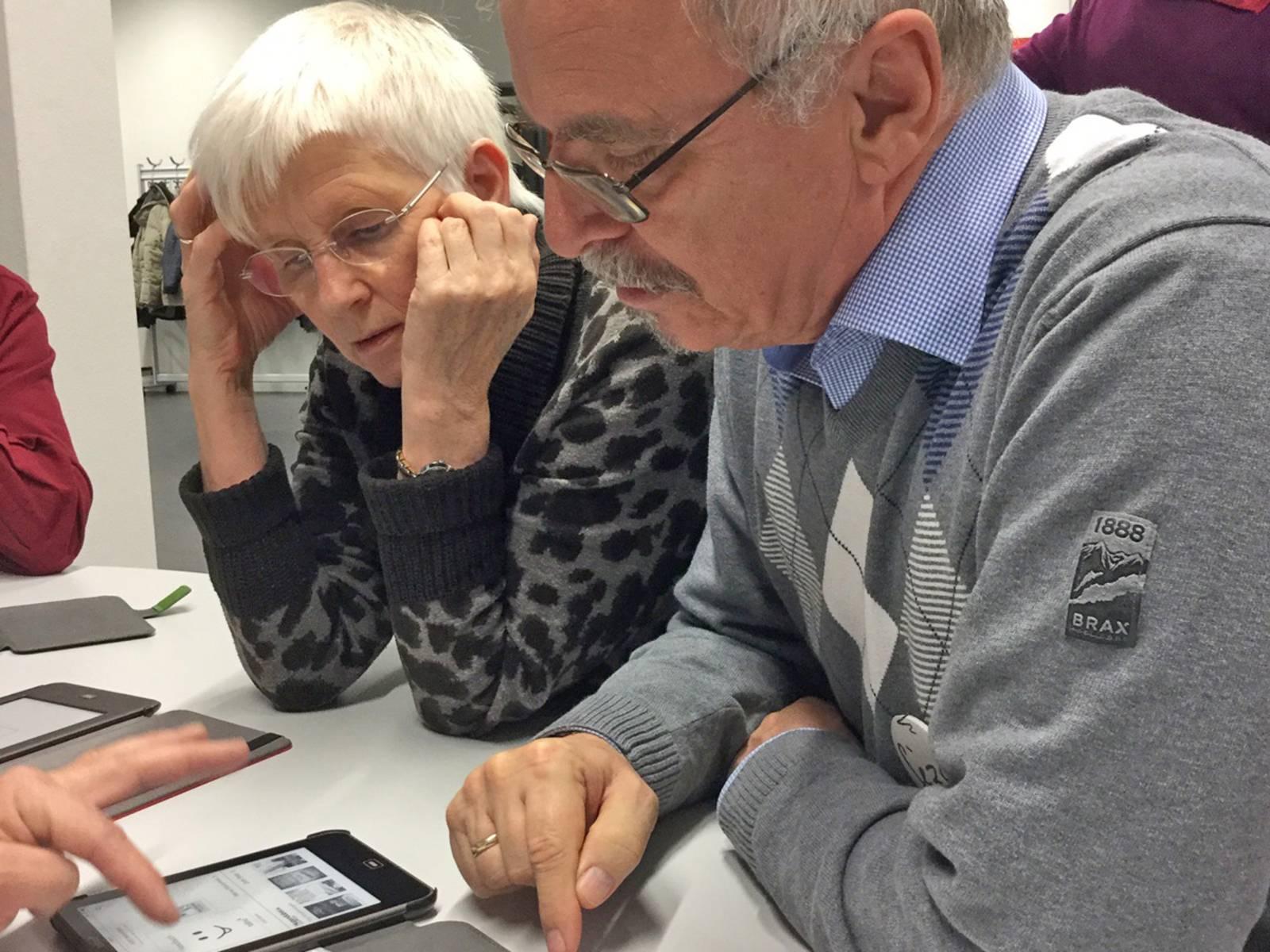 Eine ältere Dame und ein älterer Herr lassen sich die Bedienung eines mobilen Gerätes erklären.