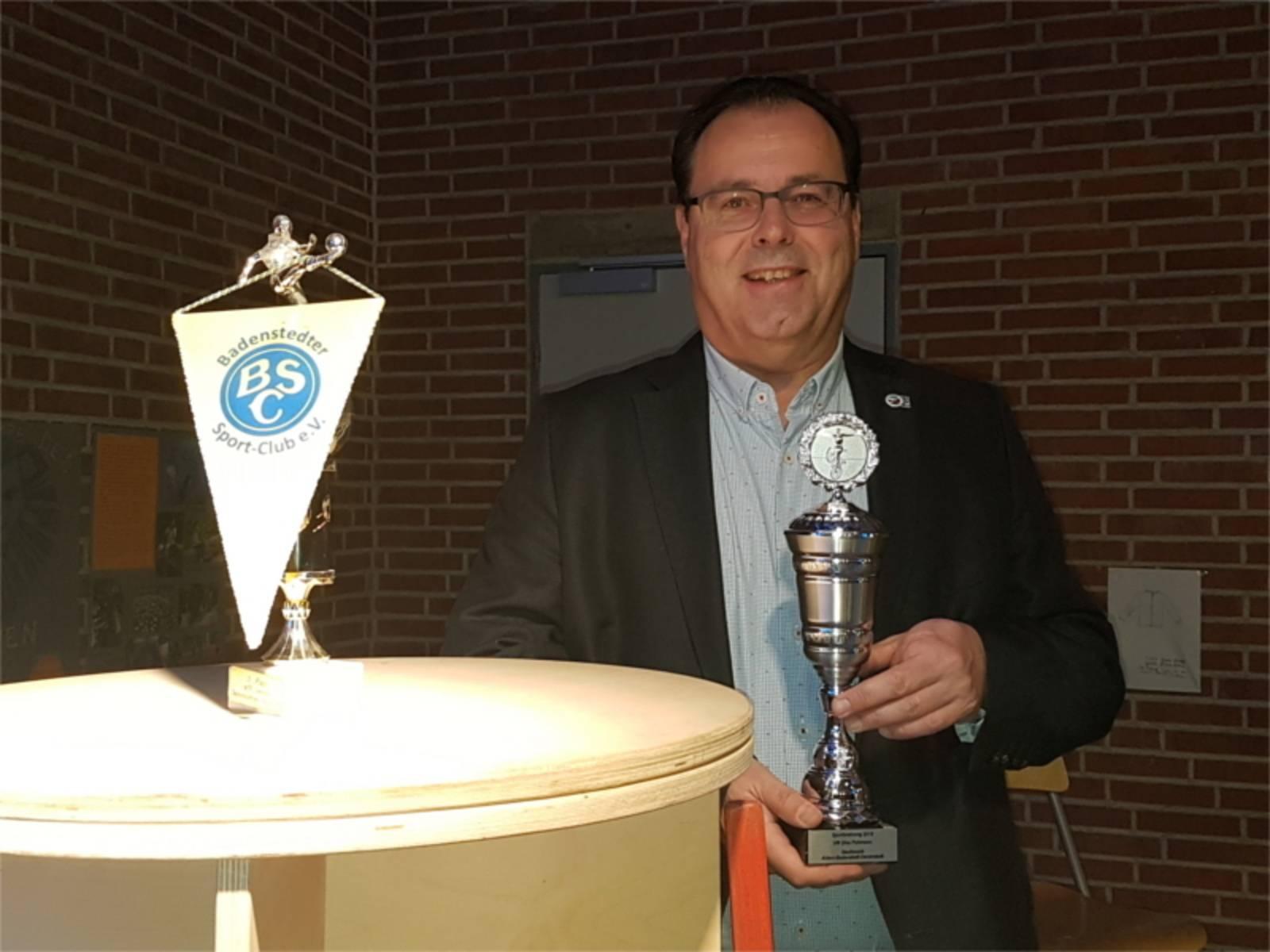 Bezirksbürgermeister Rainer Göbel übergibt Pokale an die erfolgreichen SportlerInnen.