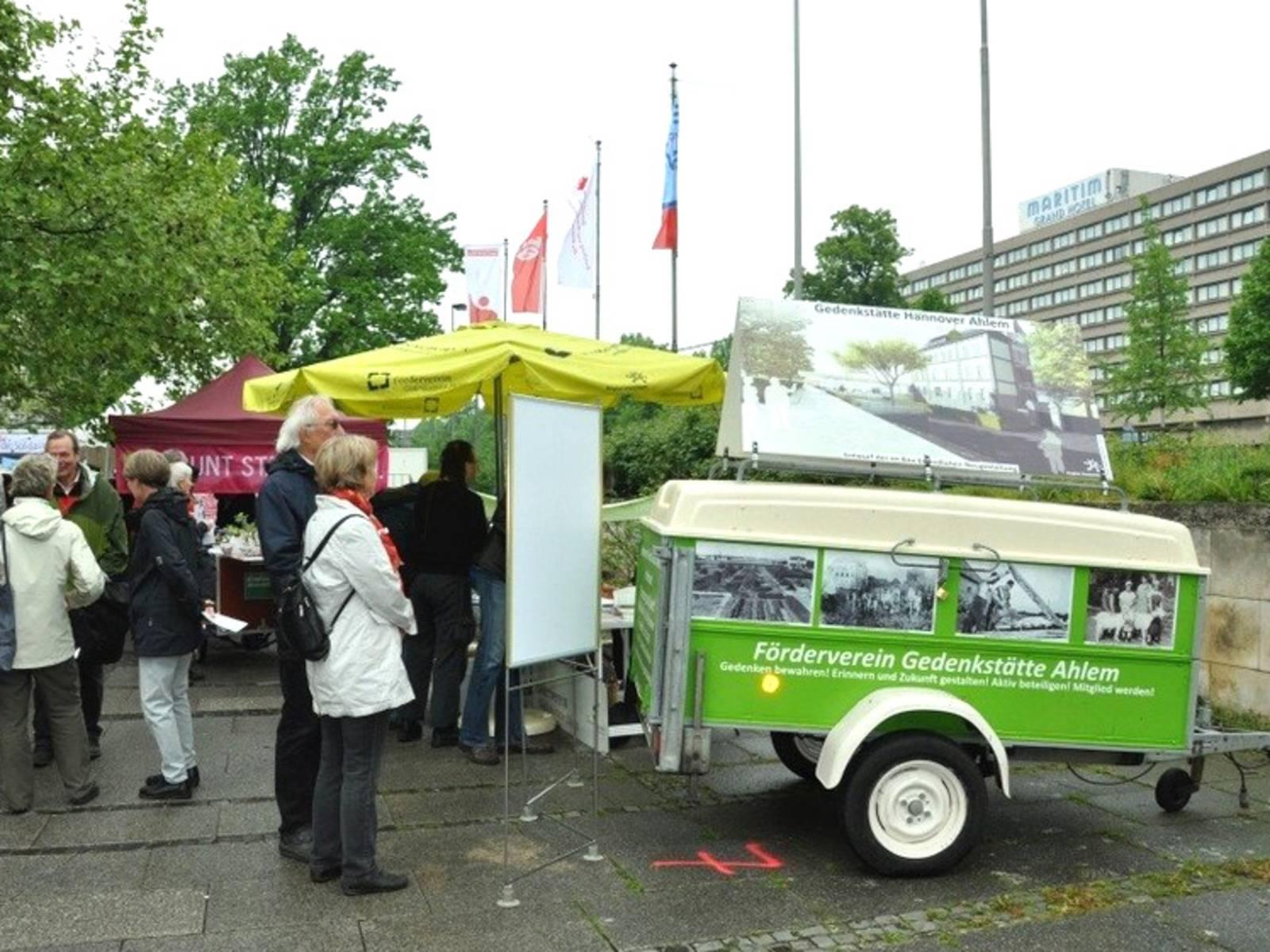Informationsstand des Fördervereins Gedenkstätte Ahlem an dem BesucherInnen stehen. Ein grüner Werbeanhänger des Fördervereins steht neben dem Infostand.