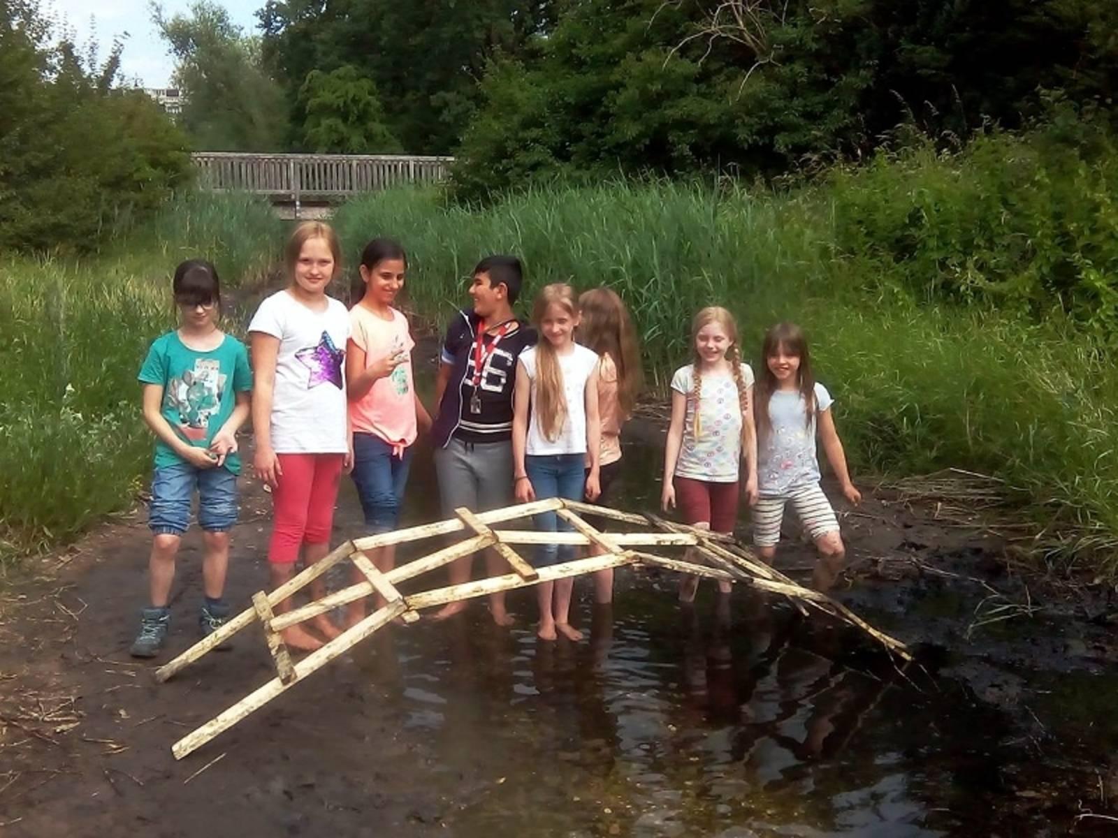 Eine Gruppe von Kindern, die in einem Bach stehen mit einer selbstgebauten Brücke.