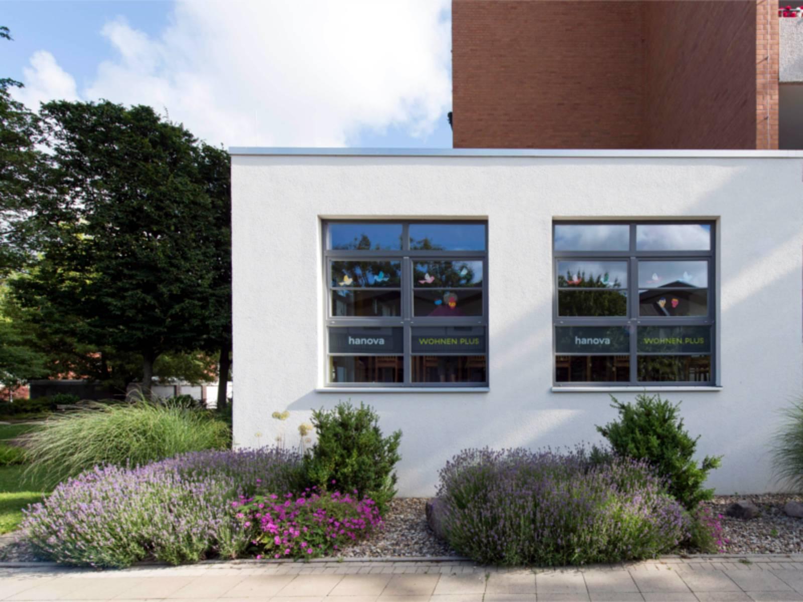 Auf dem Bild ist ein weißes Haus mit zwei großen Fenstern zu sehen.