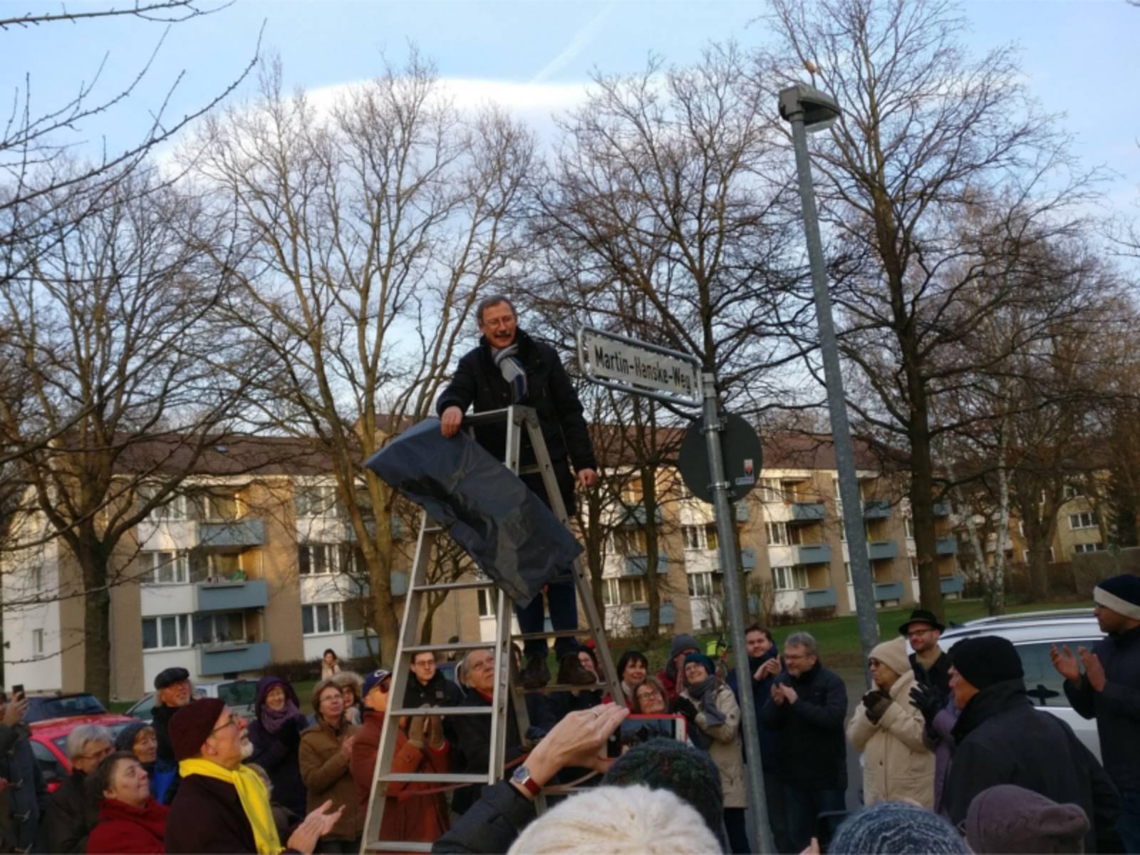 Ein Mann steht auf einer Leiter und enthüllt ein Straßenschild. Dabei stehen mehrere Personen, die dabei zusehen.