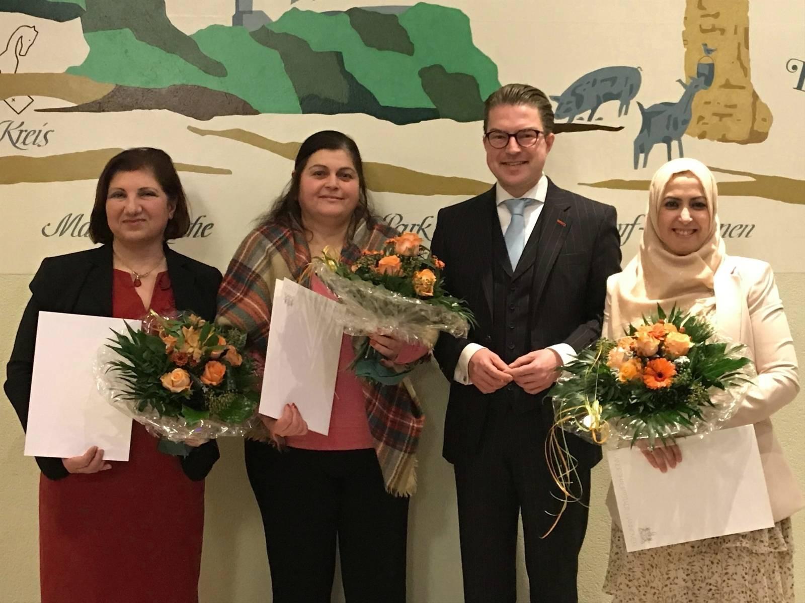 Gruppenfoto: Drei Frauen halten Urkunden und Blumensträuße in den Händen, dazwischen der Bezirksbürgermeister Henning Hofmann.
