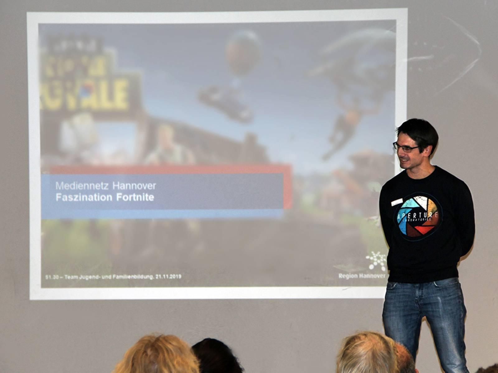 Ein Mann steht vor einer Leinwand vor Publikum und scheint einen Vortrag zu halten.