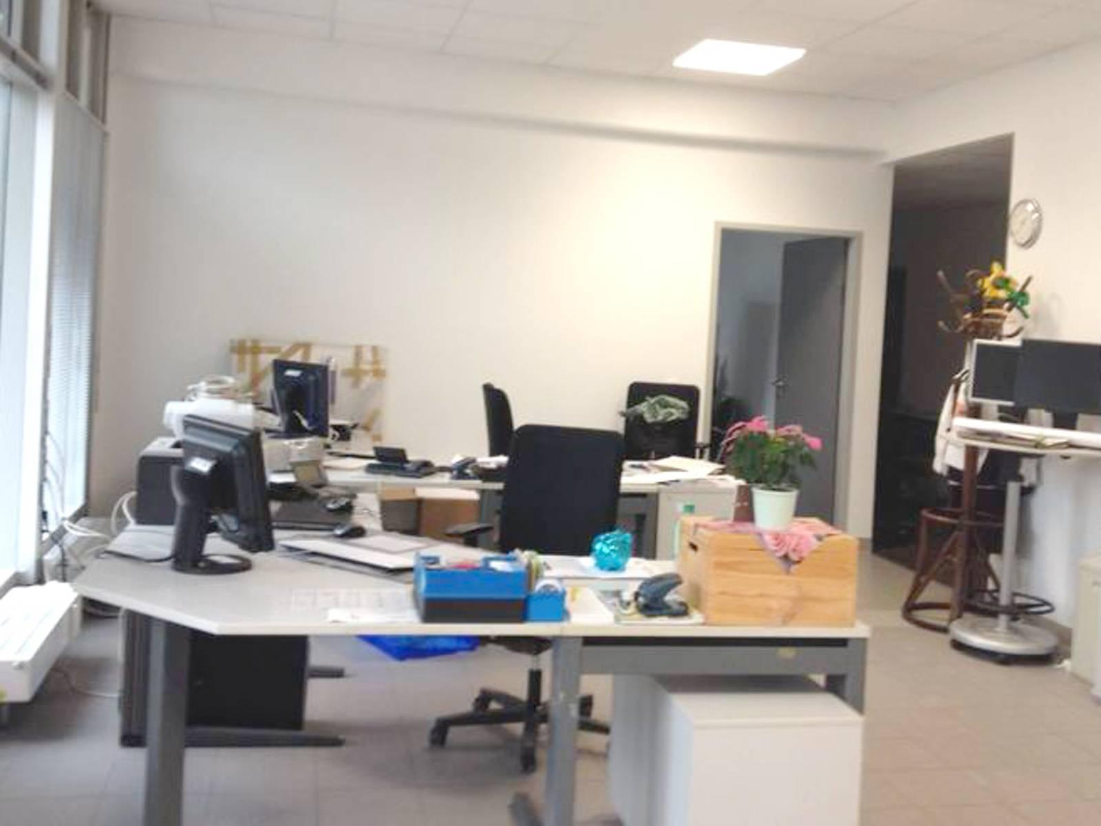 Der Blick richtet sich in das Büro - zu sehen sind zwei Schreibtischkombinationen im Vorder- und im Hinterbereich, rechts zu sehen sind 6 Aktenschränke, im hinteren Bereich rechts ein Stehtisch mit 2 Monitoren.