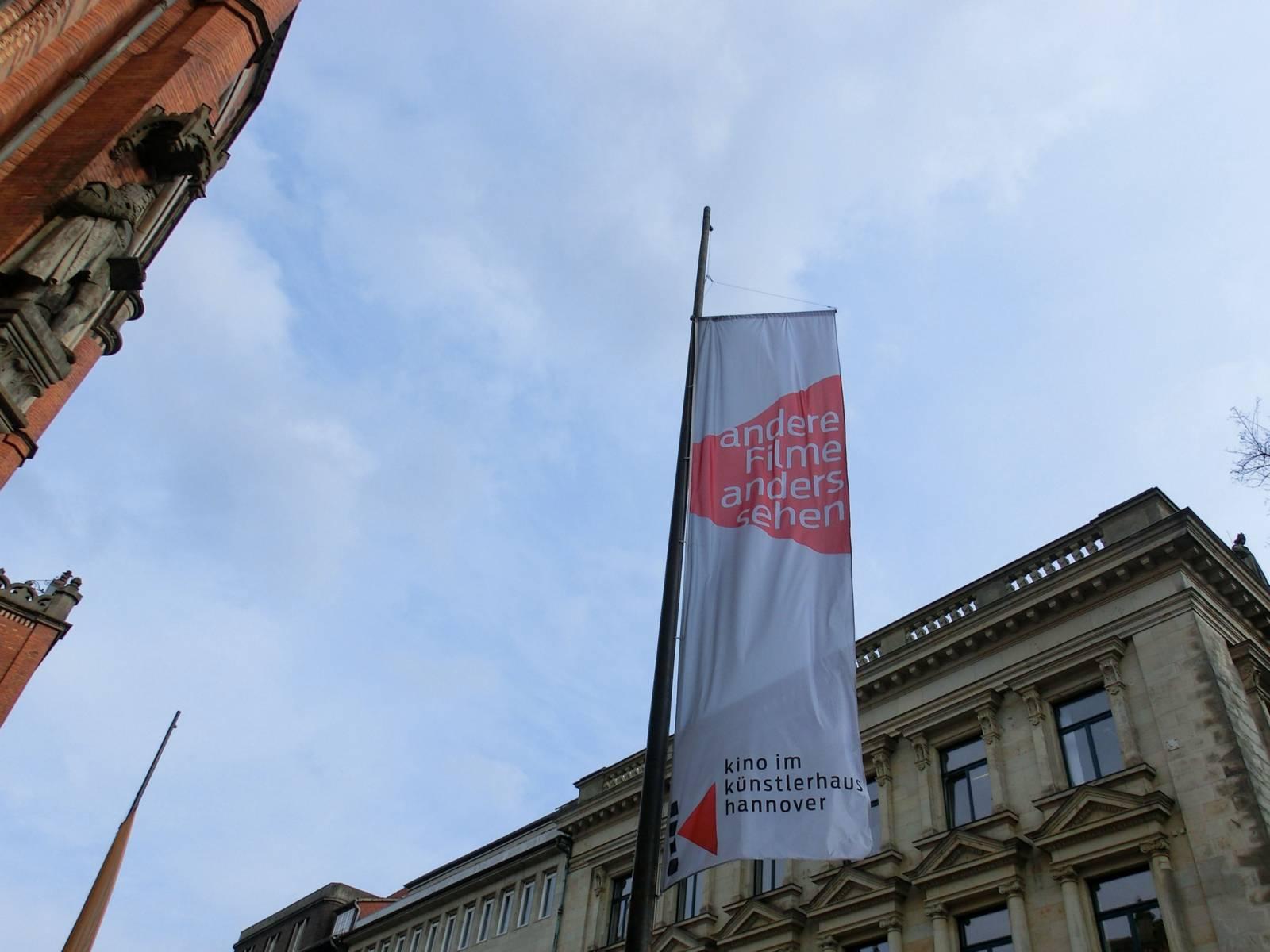 """Eine Fahne vor einem Gebäude mit der Aufschrift """"andere Filme anders sehen"""" und """"Kino im Künstlerhaus"""""""