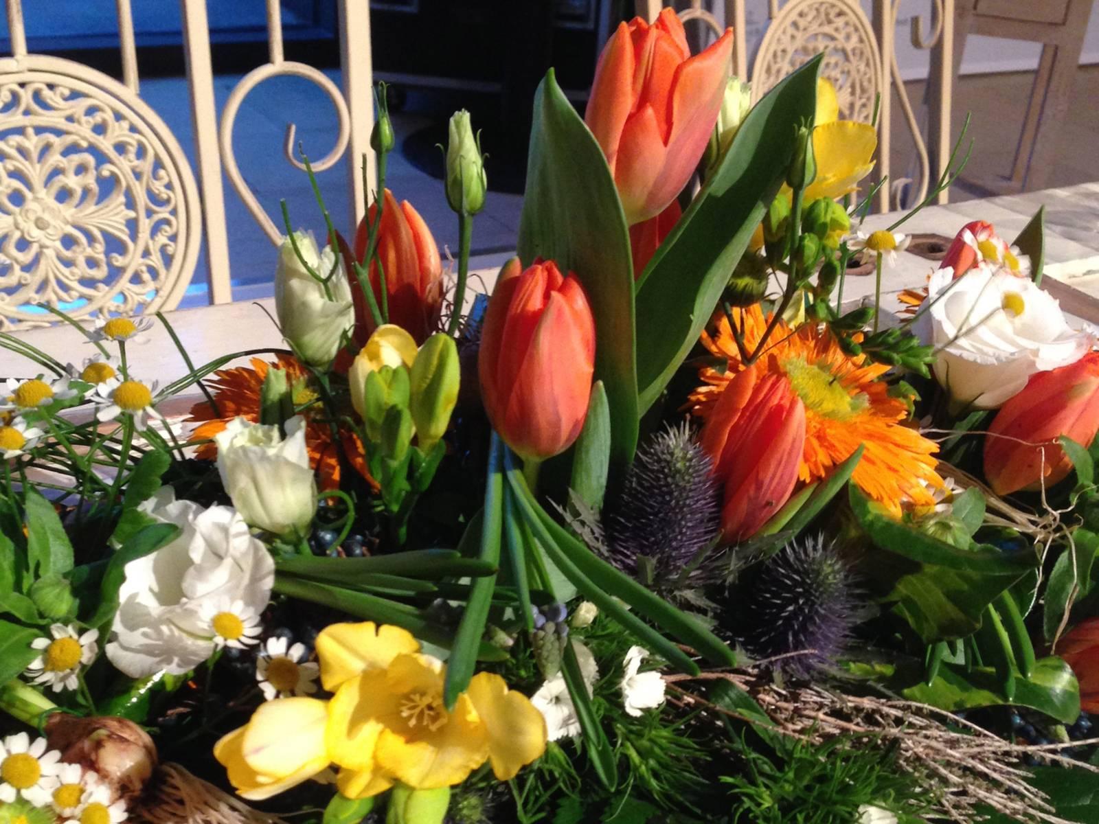 Üppiges Blumengesteck mit Tulpen, Fresien, Rosen und Schmuckpflanzen