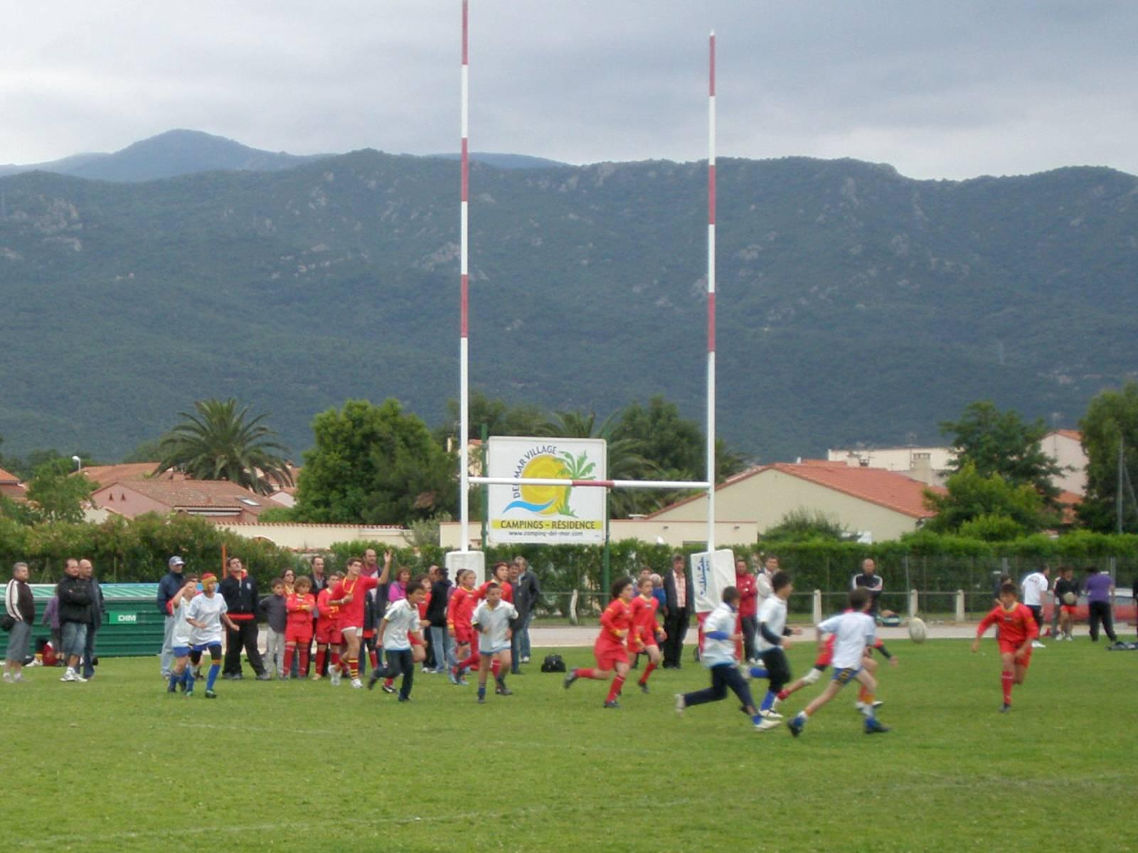Jugendliche zweier Mannschaften jagen einem Rugby-Ball hinterher