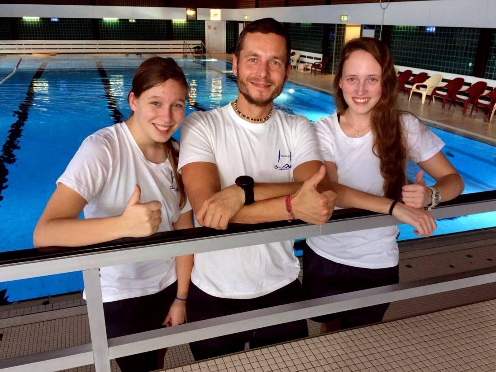 Zwei Frauen und ein Mann in einer Schwimmhalle.