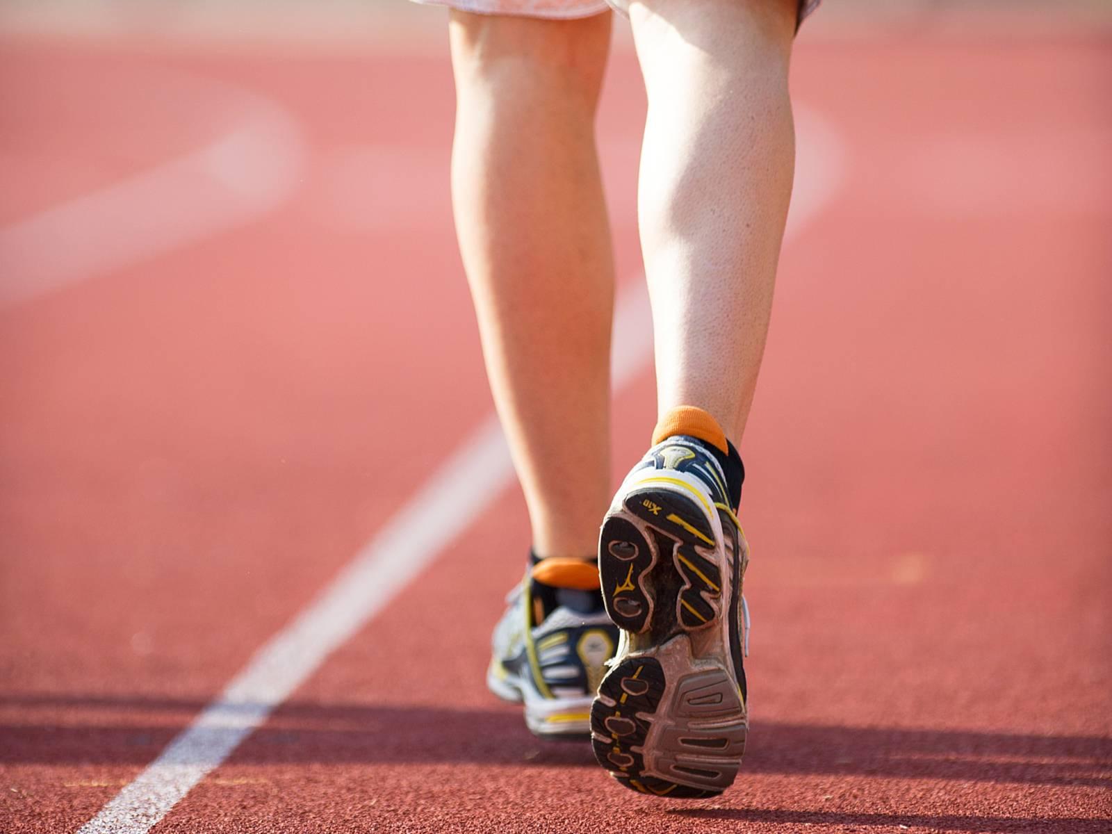 Beine eines Sportlers beim Laufen auf einem Sportplatz.