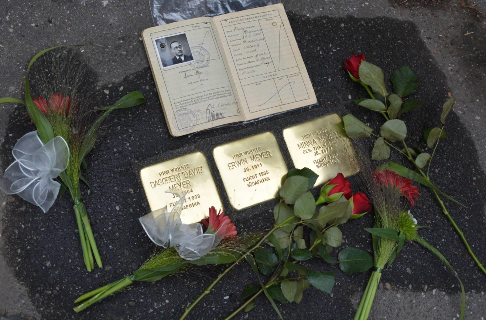 """Stolpersteinverlegung in der Heinrich-Stamme-Str. 3: Dagobert """"David"""", Minna und deren Sohn Erwin Meyer, dessen Ausweis von Angehörigen mitgebracht wurde."""