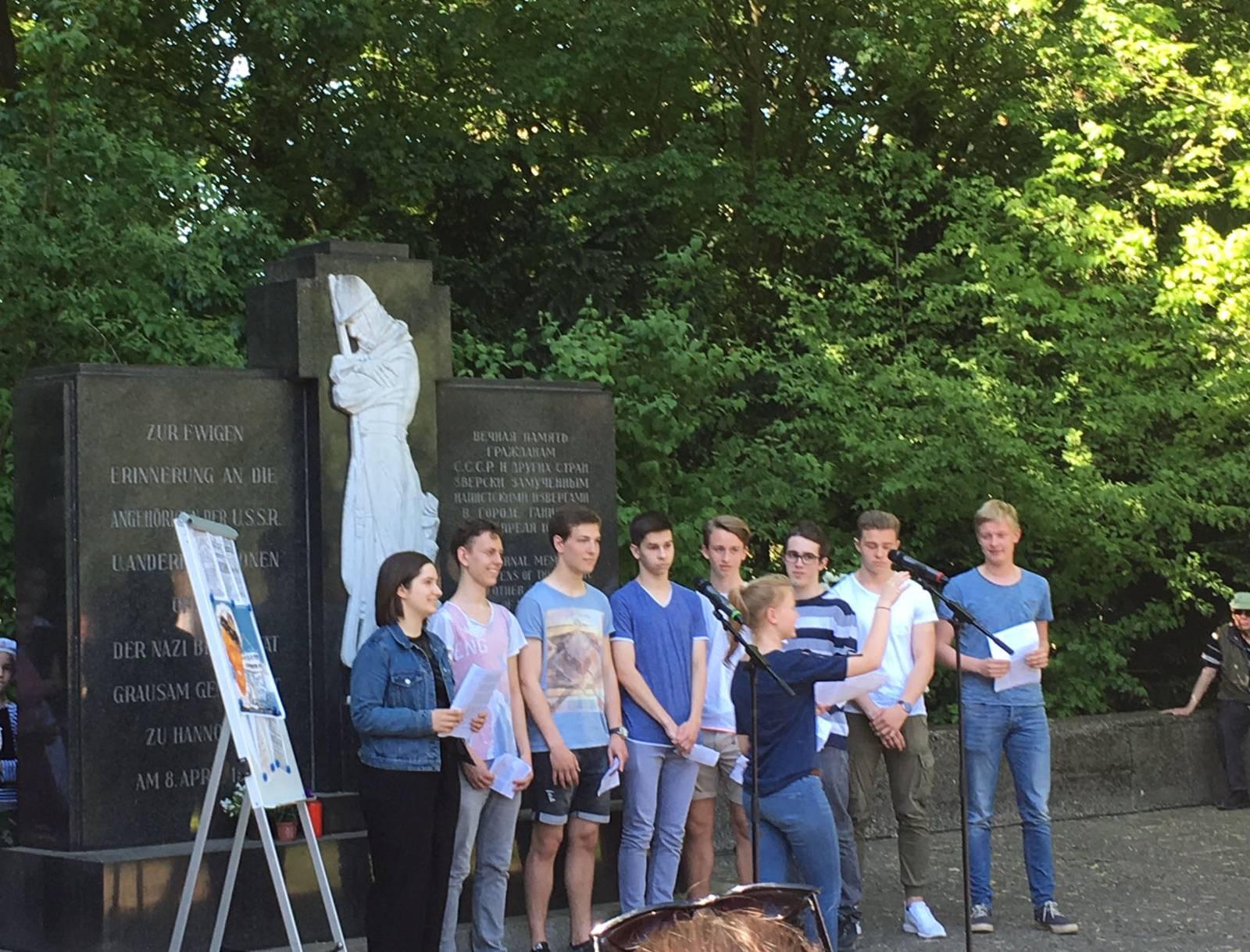 Eine Gruppe Jugendlicher vor einem Mahnmal