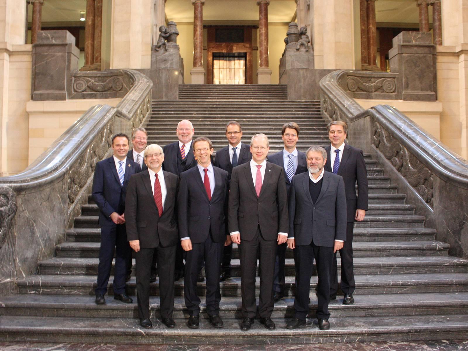 Zehn Männer auf der Rathaustreppe