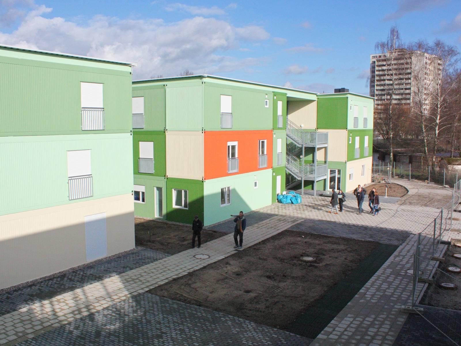 Die Flüchtlingsunterkunft besteht aus zwei- und dreigeschossigen Wohngebäuden und zum Teil eingeschossigen Gemeinschafts- und Verwaltungsgebäuden