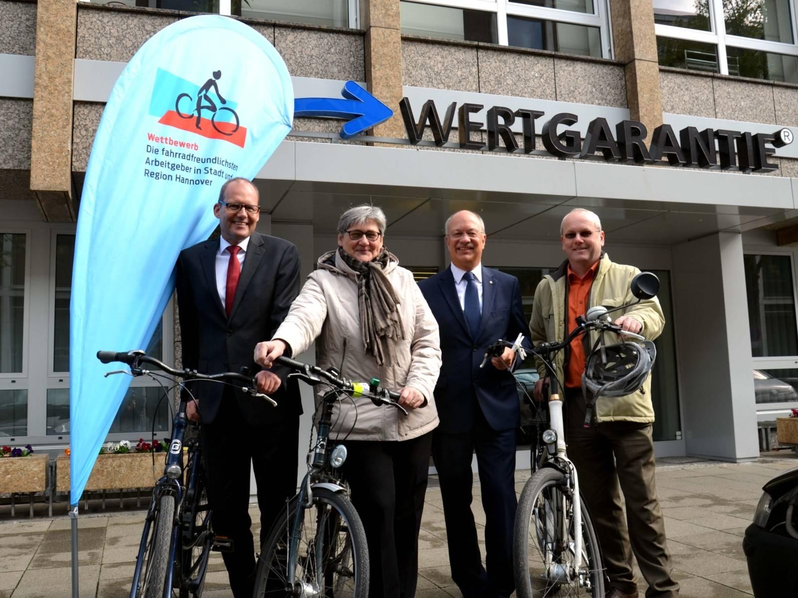 Drei Männer und eine Frau mit Fahrrädern.