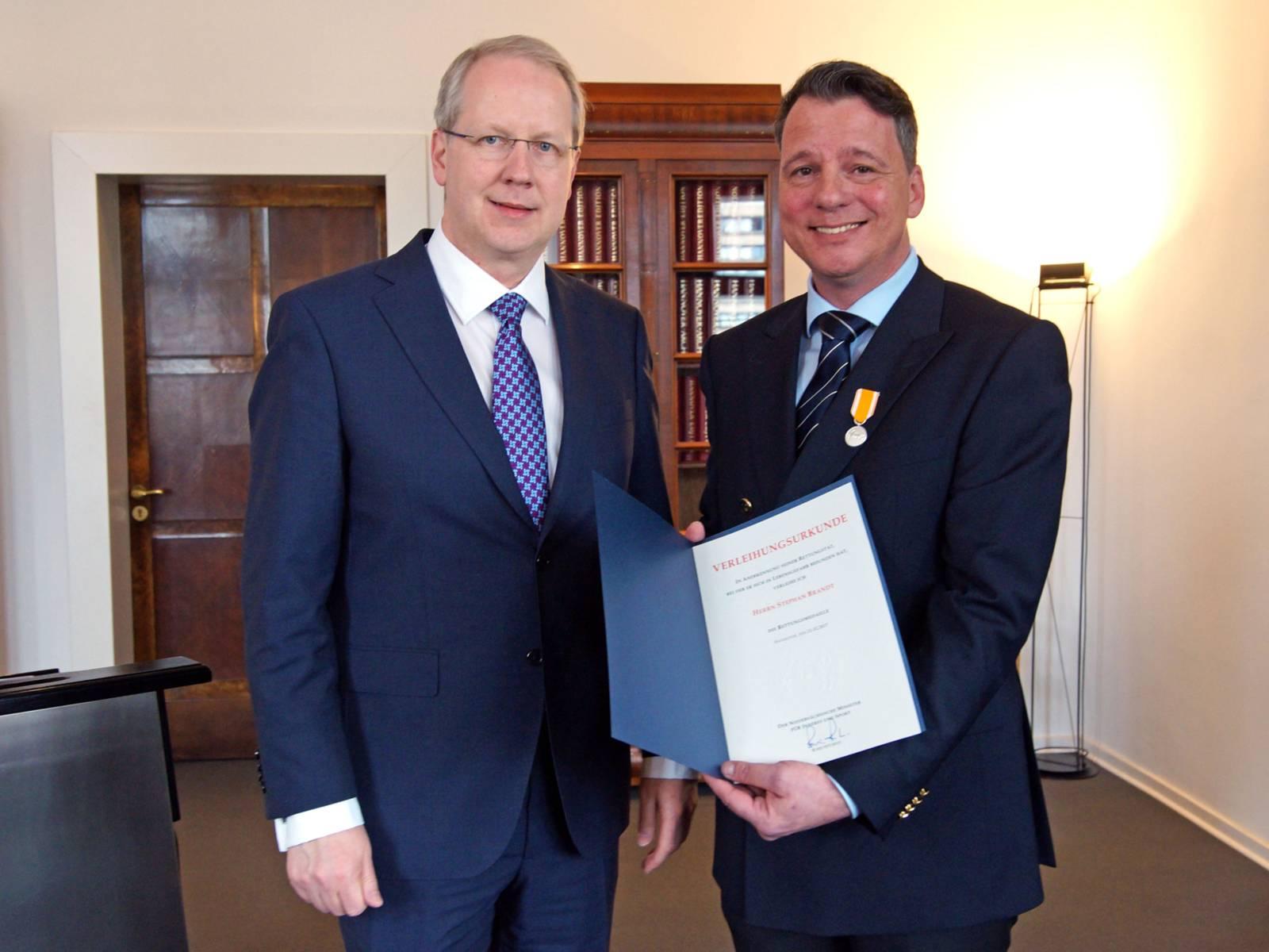 Zwei Männer mit einer Auszeichnung.