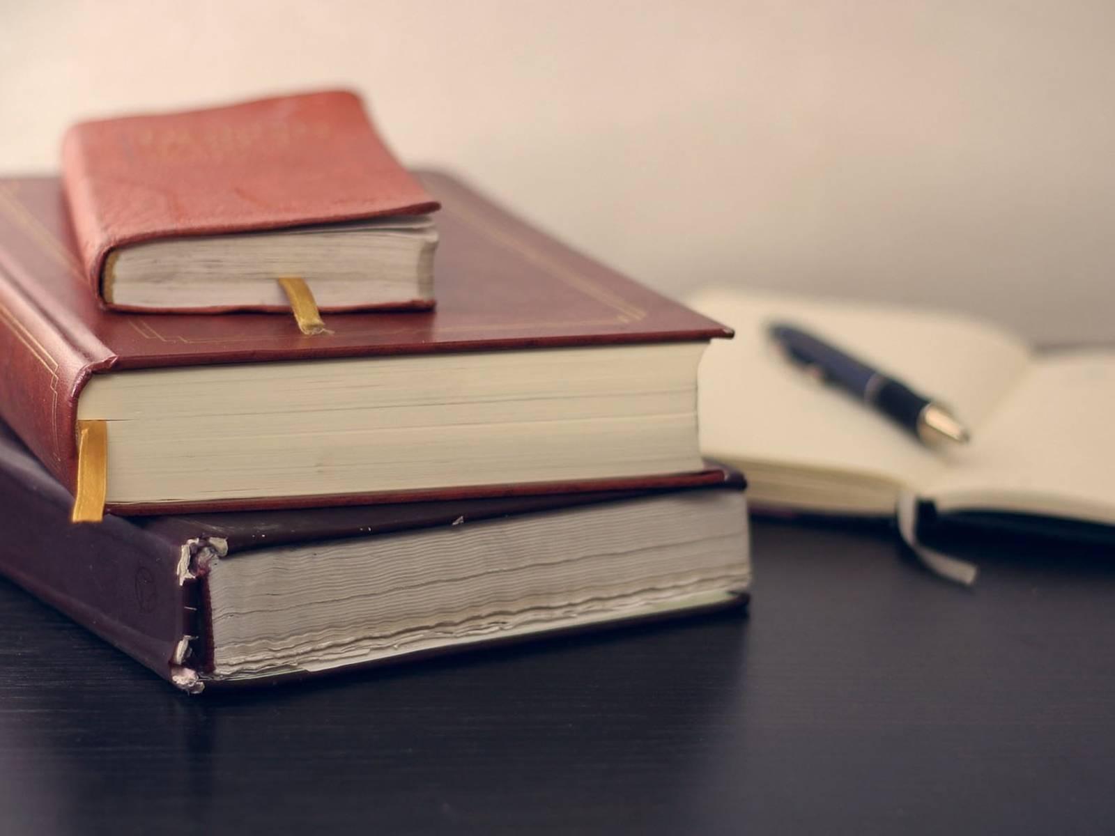 Ein Stapel Bücher und ein Notizblock mit Stift.