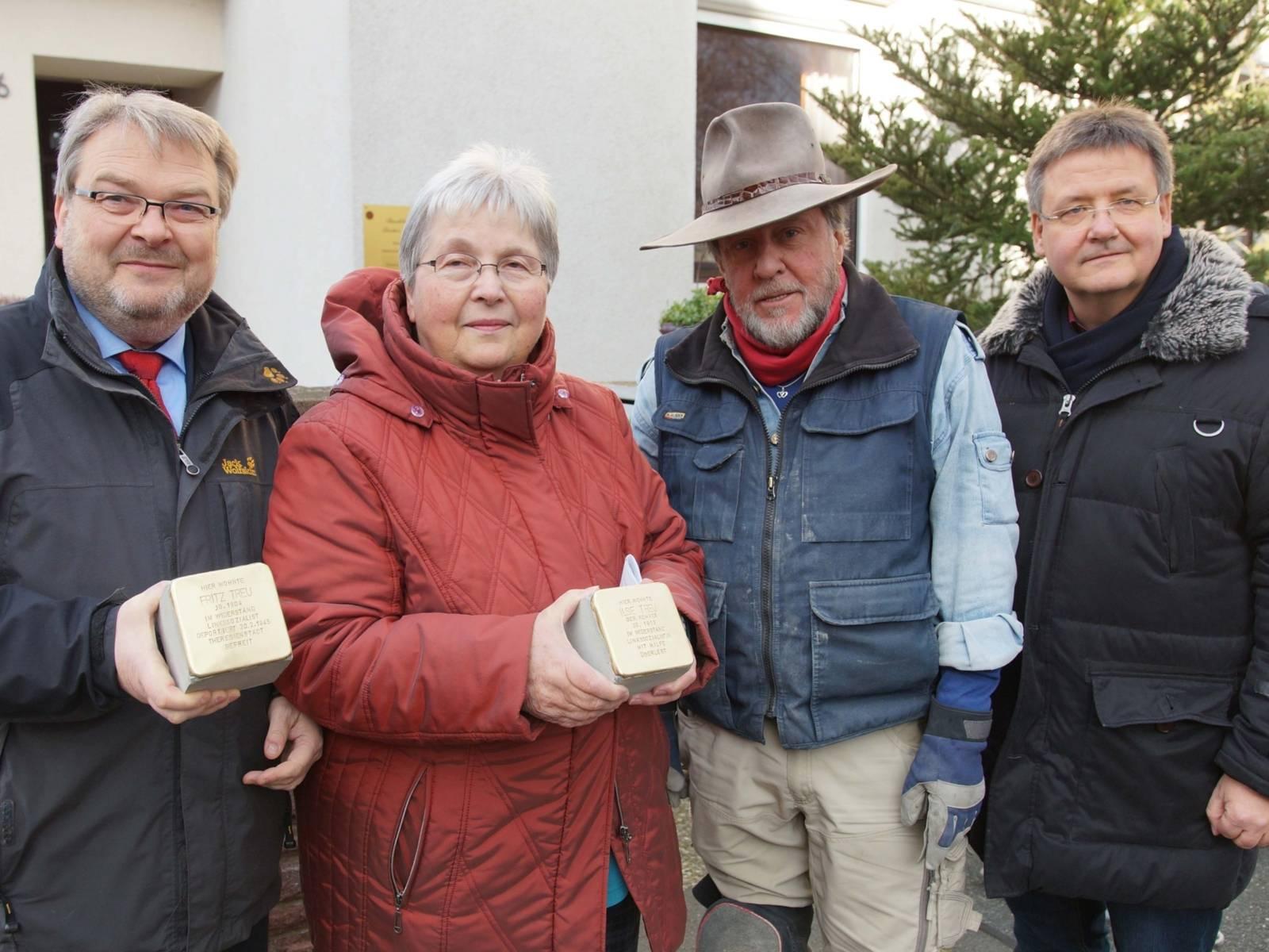 Drei Männer und eine Frau mit zwei Stolpersteinen.