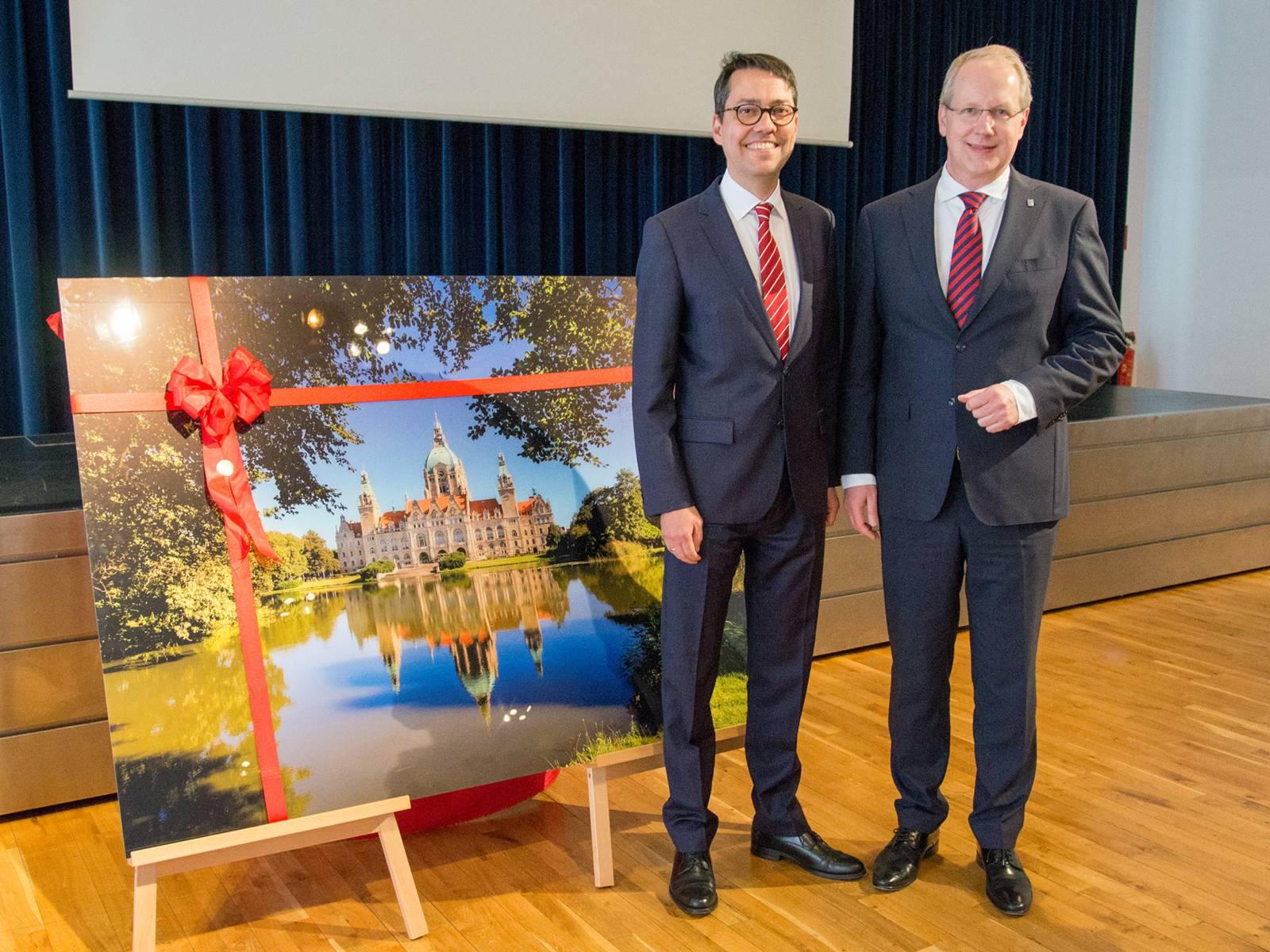 Prof. Dr. Marc Hansmann und Oberbürgermeister Stefan Schstok neben einem großen Acryl-Druck des Neuen Rathauses