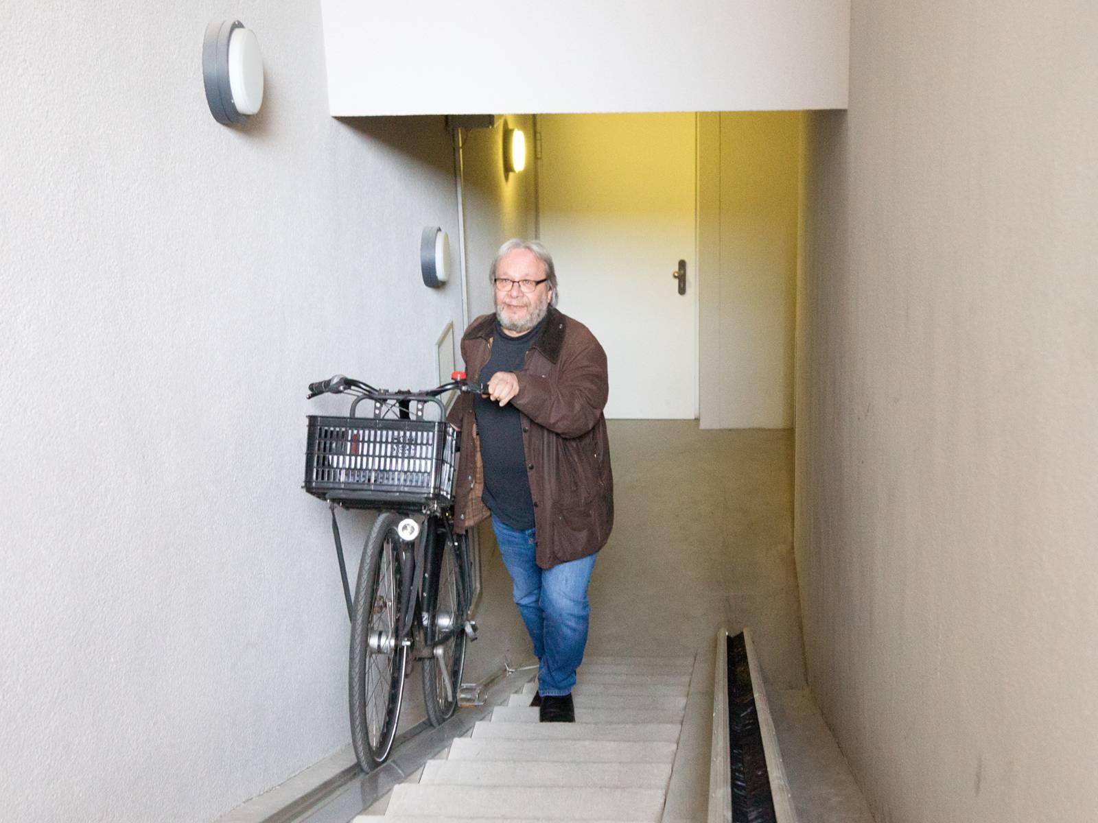 Michael Guttmann bewegt ein Fahrrad mittels des Rinne-Förderbands aufwärts