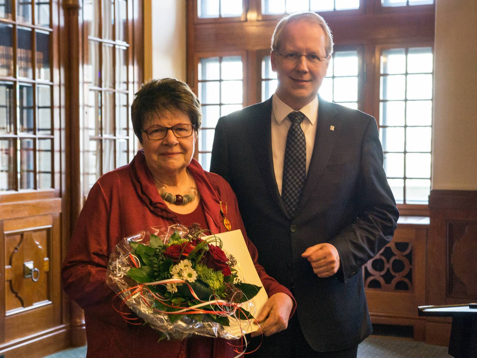 Frau und Mann mit Blumen und einer Urkunde.