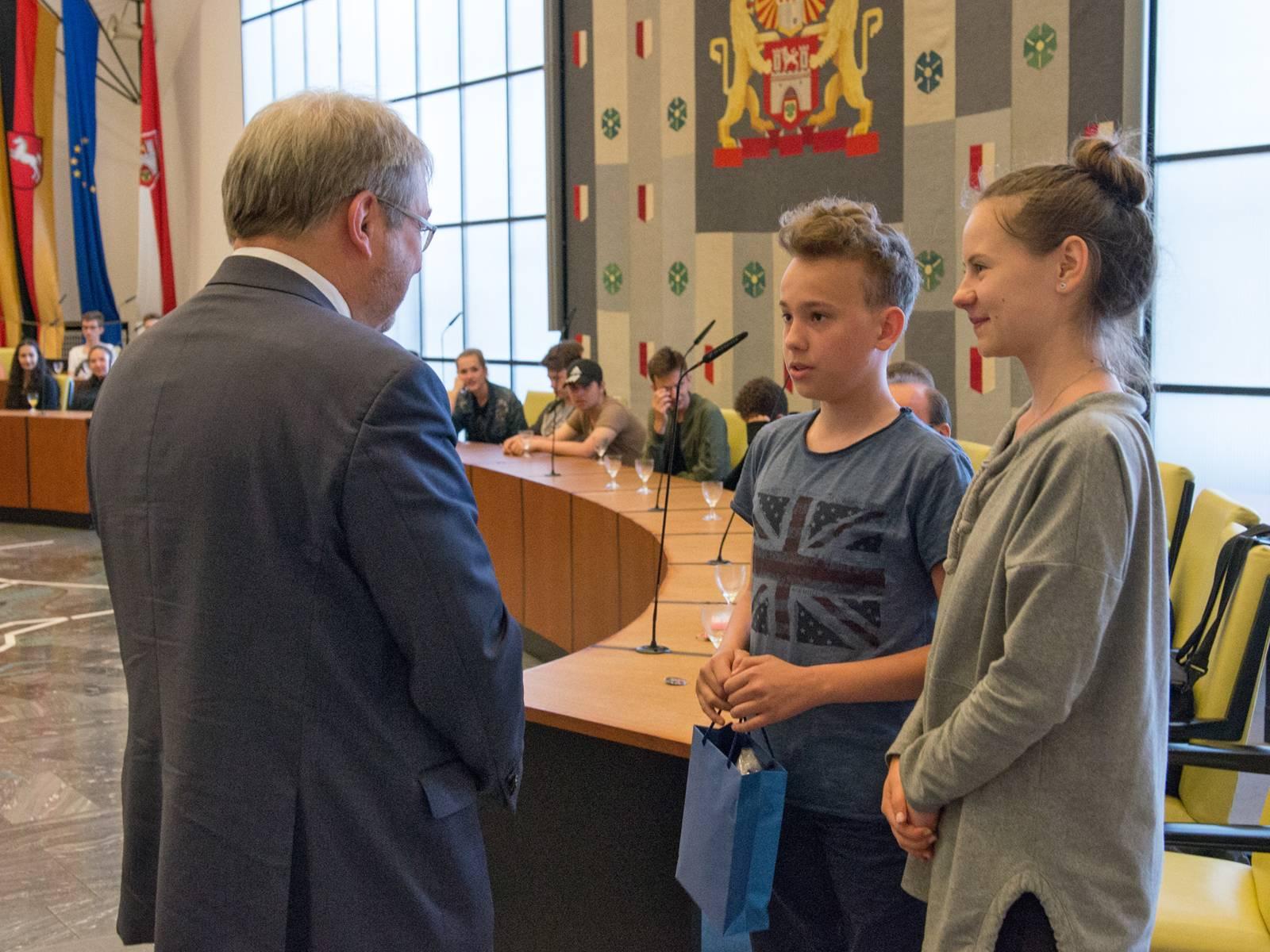 Zwei Jugendliche übergeben eine Geschenktasche an Bürgermeister Hermann