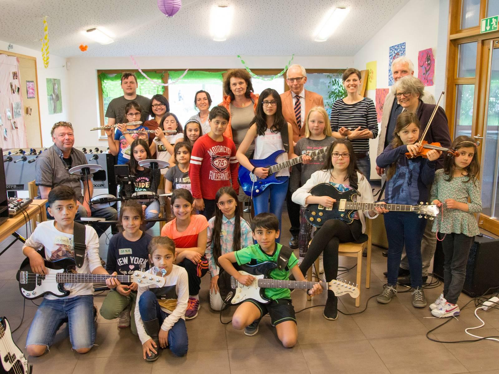 Eine größere Gruppe Kinder sowie einige Erwachsene in einem Raum voller Musikinstrumente