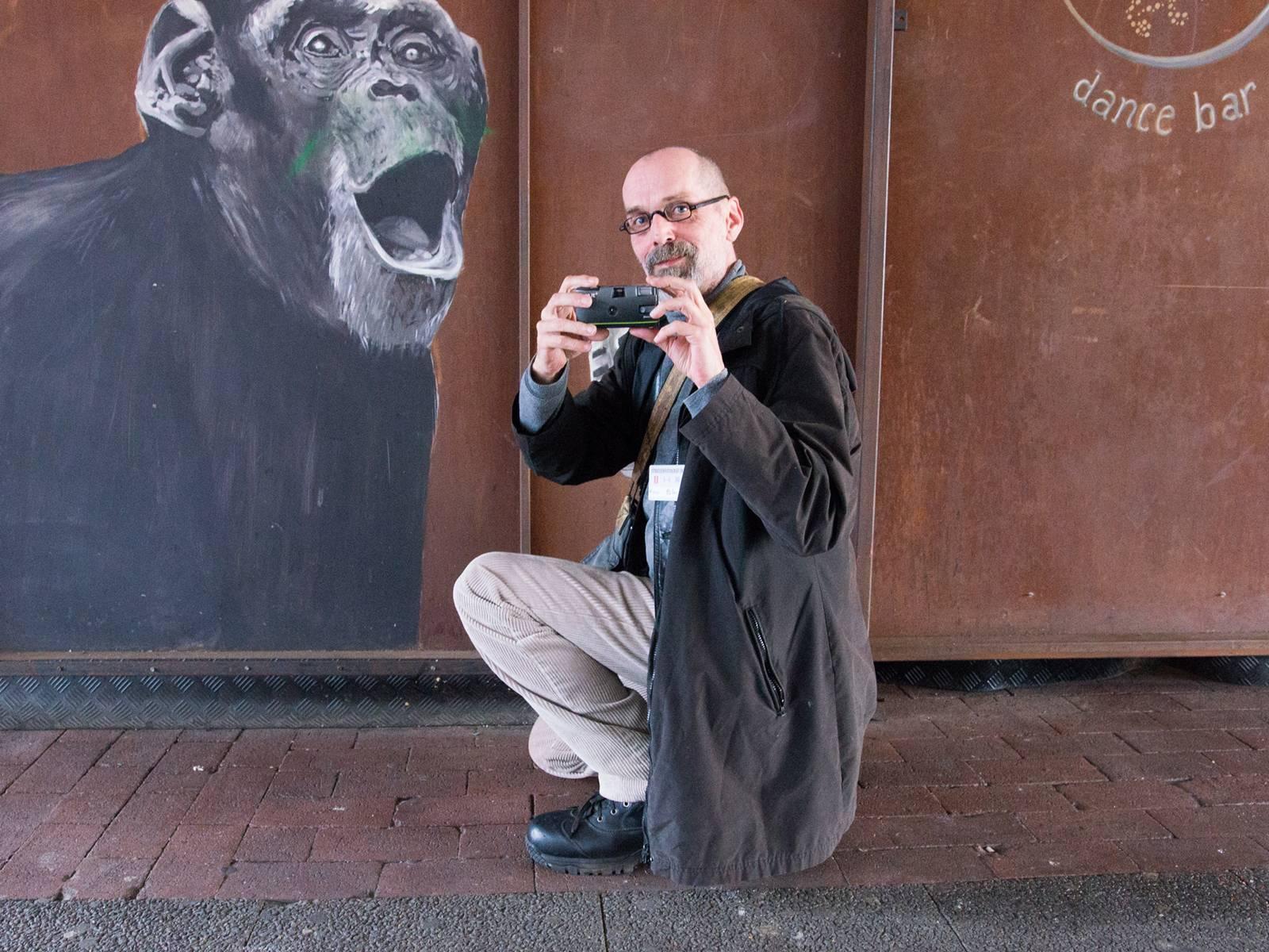 Ein Mann hält eine Fotokamera in der Hand und kniet vor einer Wandmalerei